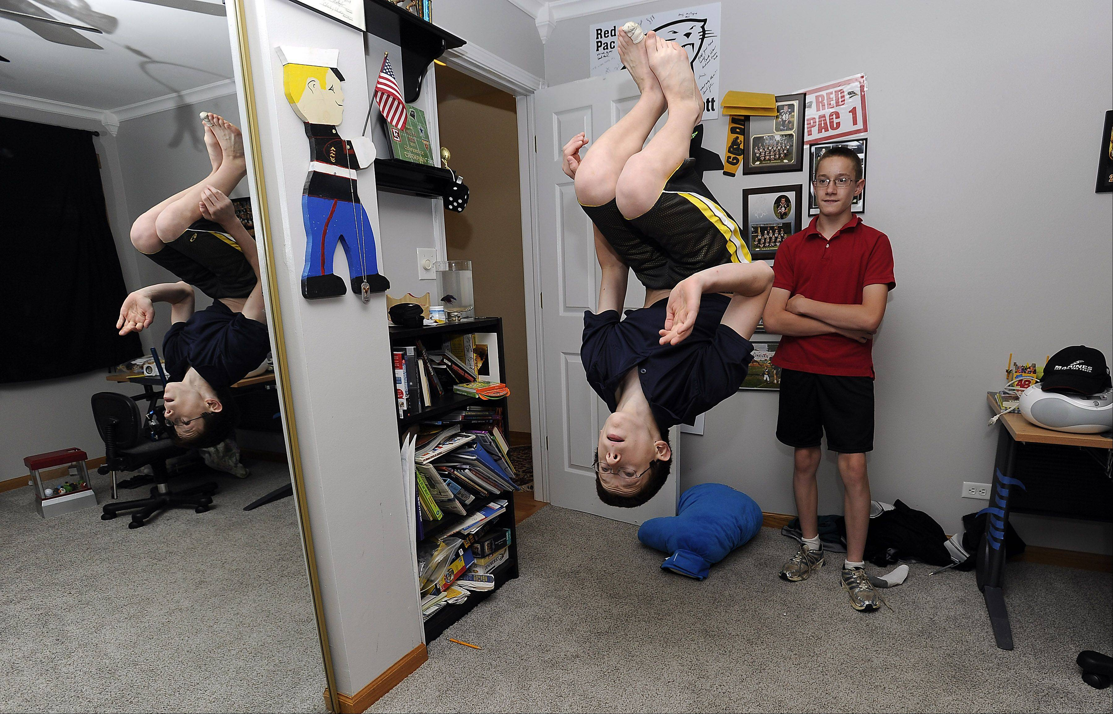 Jack McDermott shows his brother Matt, both 13, his latest gymnastics move in their Hoffman Estates home. The boy' parents are taking them back to their native Russia this summer to help them learn about their culture and history.