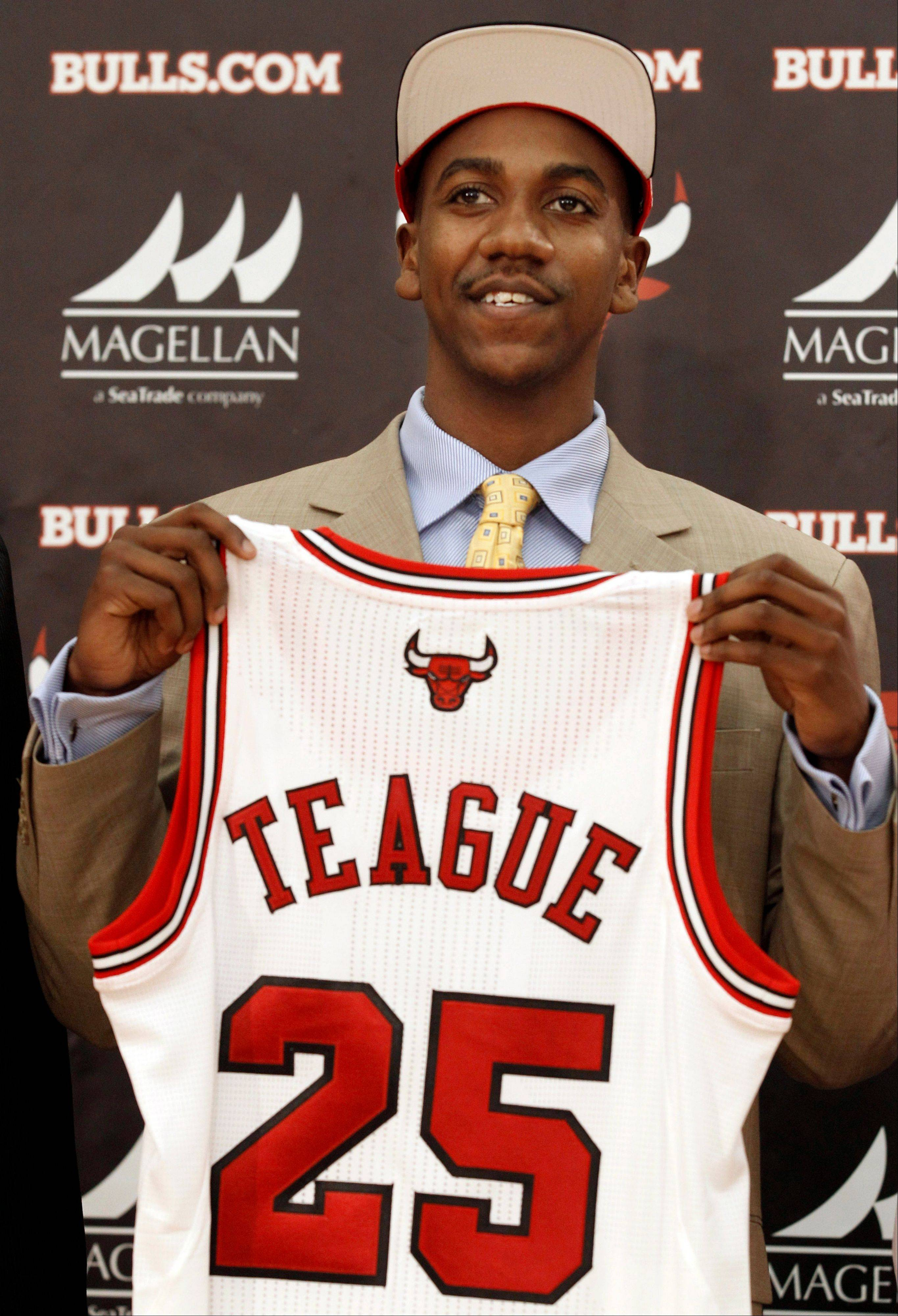 Marquis Teague holds up his new jersey during a Bulls news conference Monday at the Berto Center.