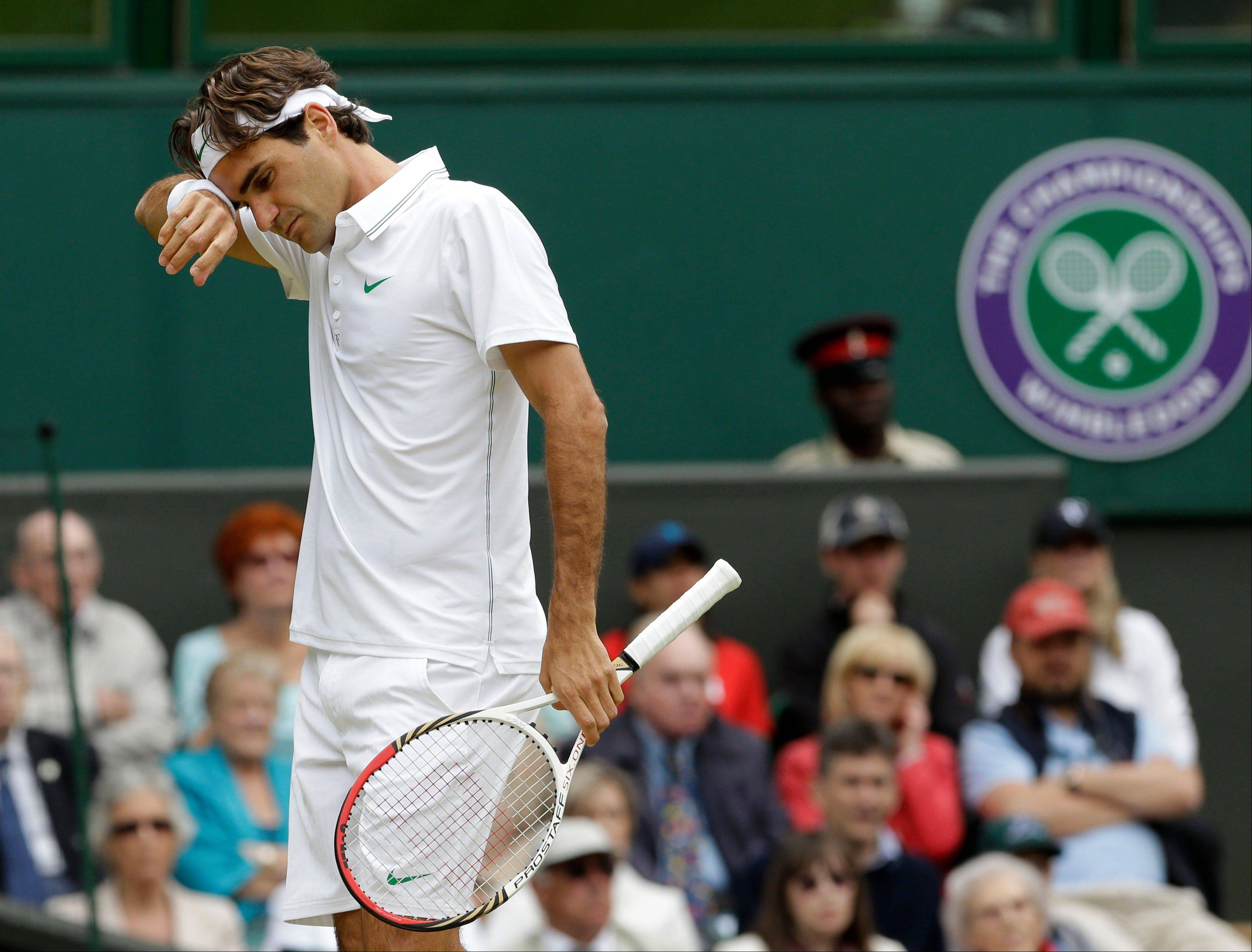 Roger Federer of Switzerland wipes his face during a fourth round singles match Monday against Xavier Malisse of Belgium at the All England Lawn Tennis Championships at Wimbledon, England. Federer needed assistance from a trainer for his back during the match.