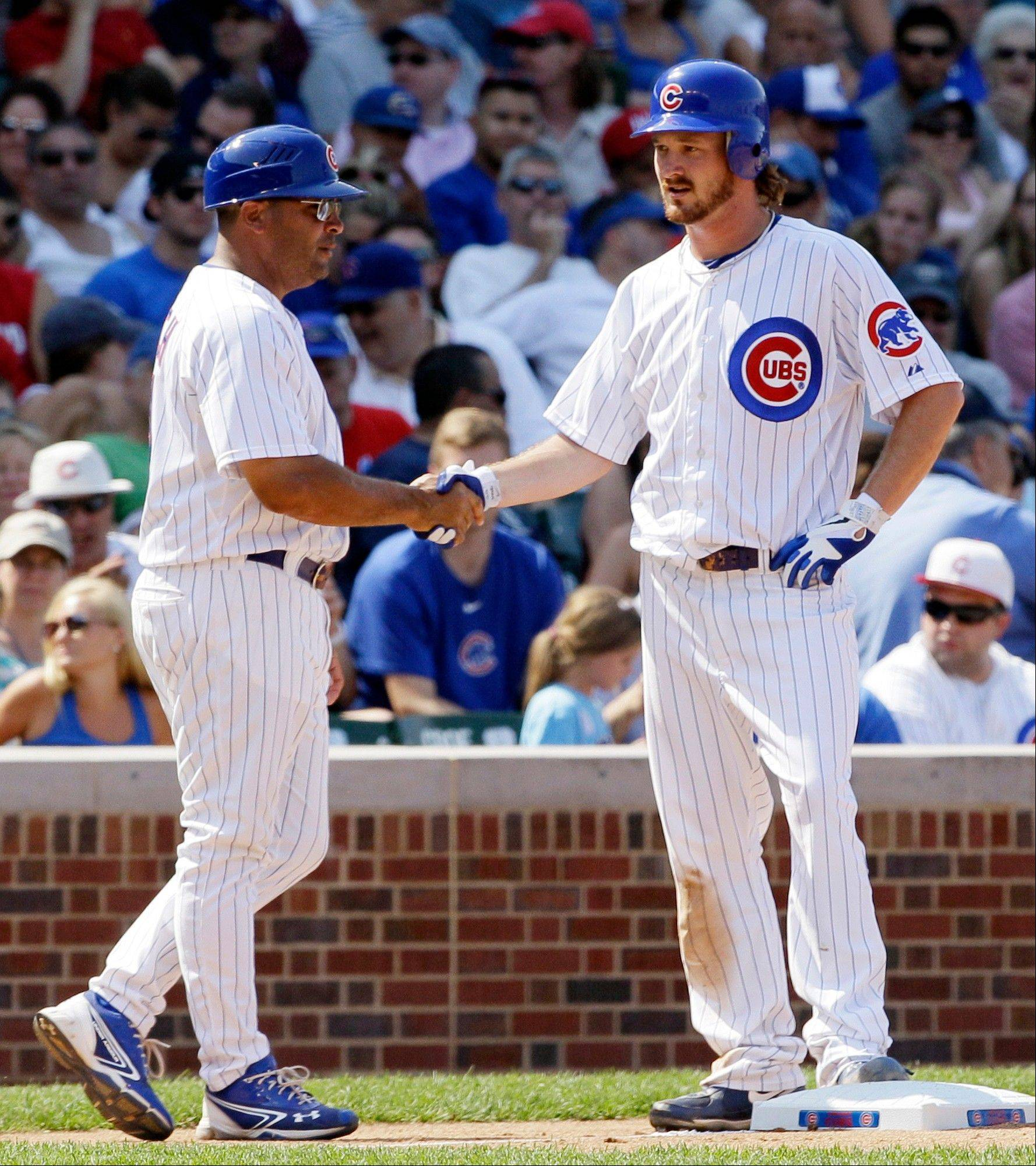 While Cubs pitcher Travis Wood, right, didn't make the club out of spring training, he is a key part of it now. Wood won his third straight game on Sunday.