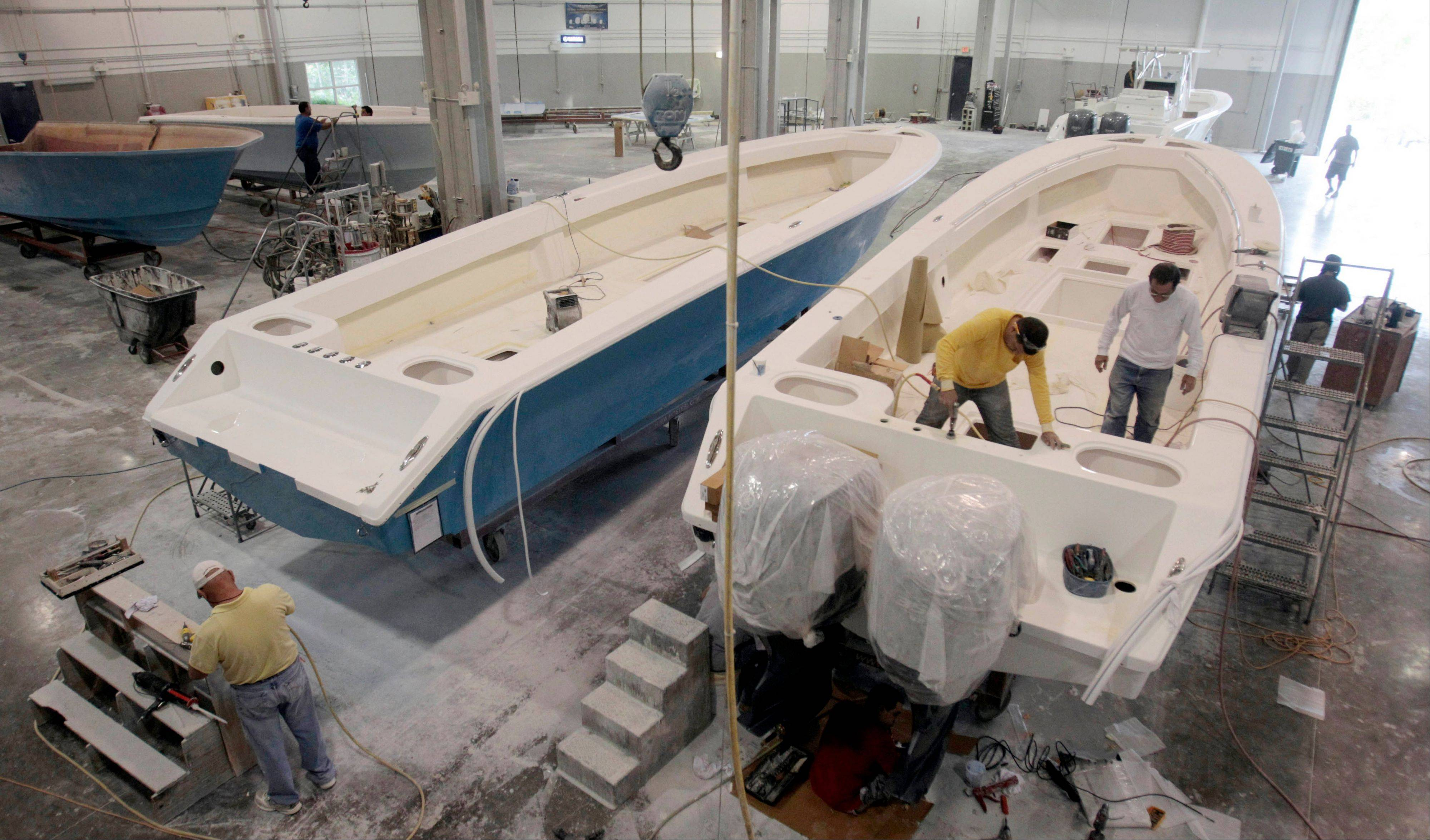Boat builders work on SeaHunter hulls at SeaHunter Boats, for delivery in Princeton, Fla. Companies placed more orders with U.S. factories in May from April, demanding more computers, machinery and other equipment that signal investment plans.
