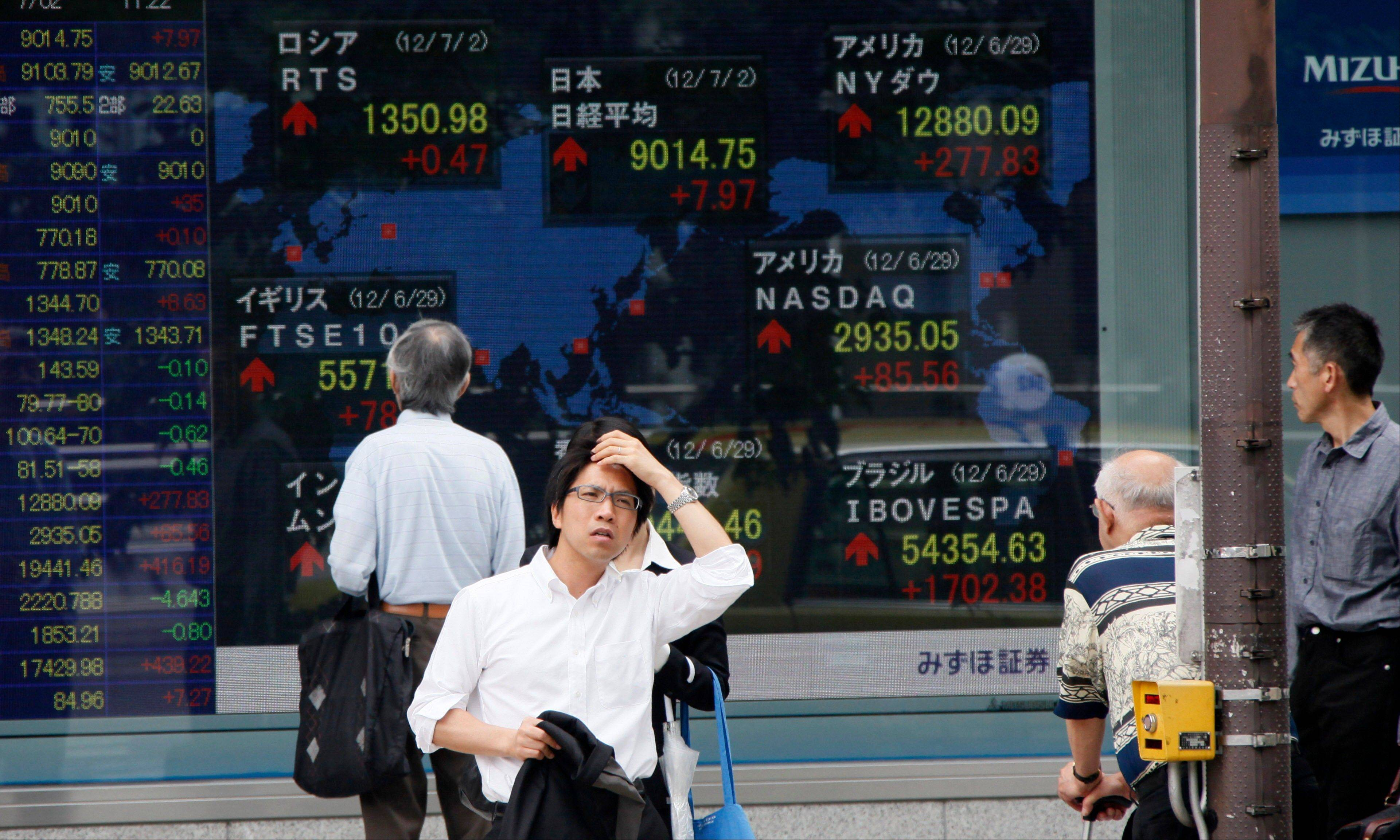 A man waits to cross a road as others watch a digital display of global stock indexes outside a securities firm in Tokyo.