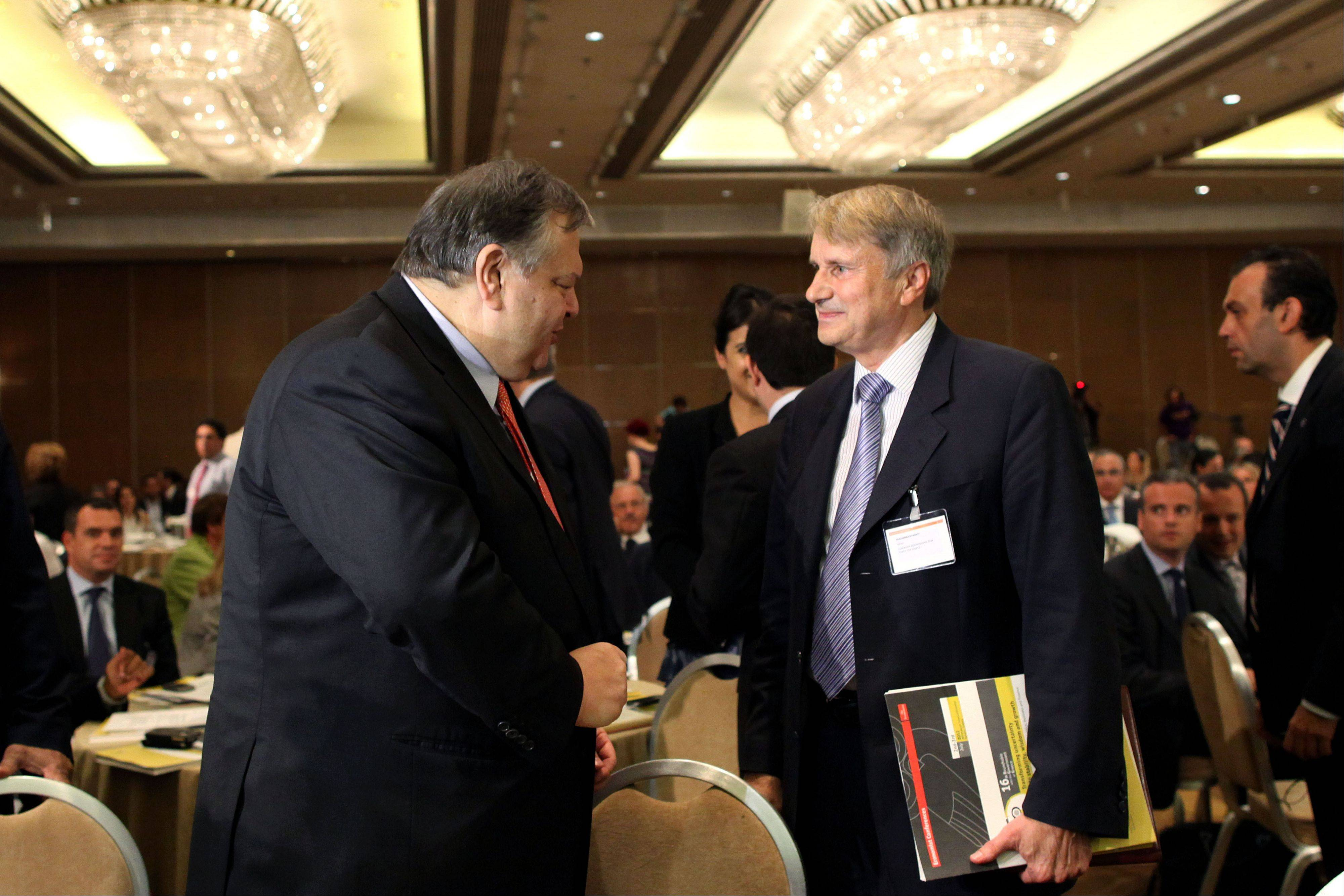 Horst Reichenbach head of the Task Force of the European Commission in charge of providing technical assistance to Greece, right, talks with Leader of the Socialist PASOK party Evangelos Venizelos during an Economist conference in Athens, on Tuesday.