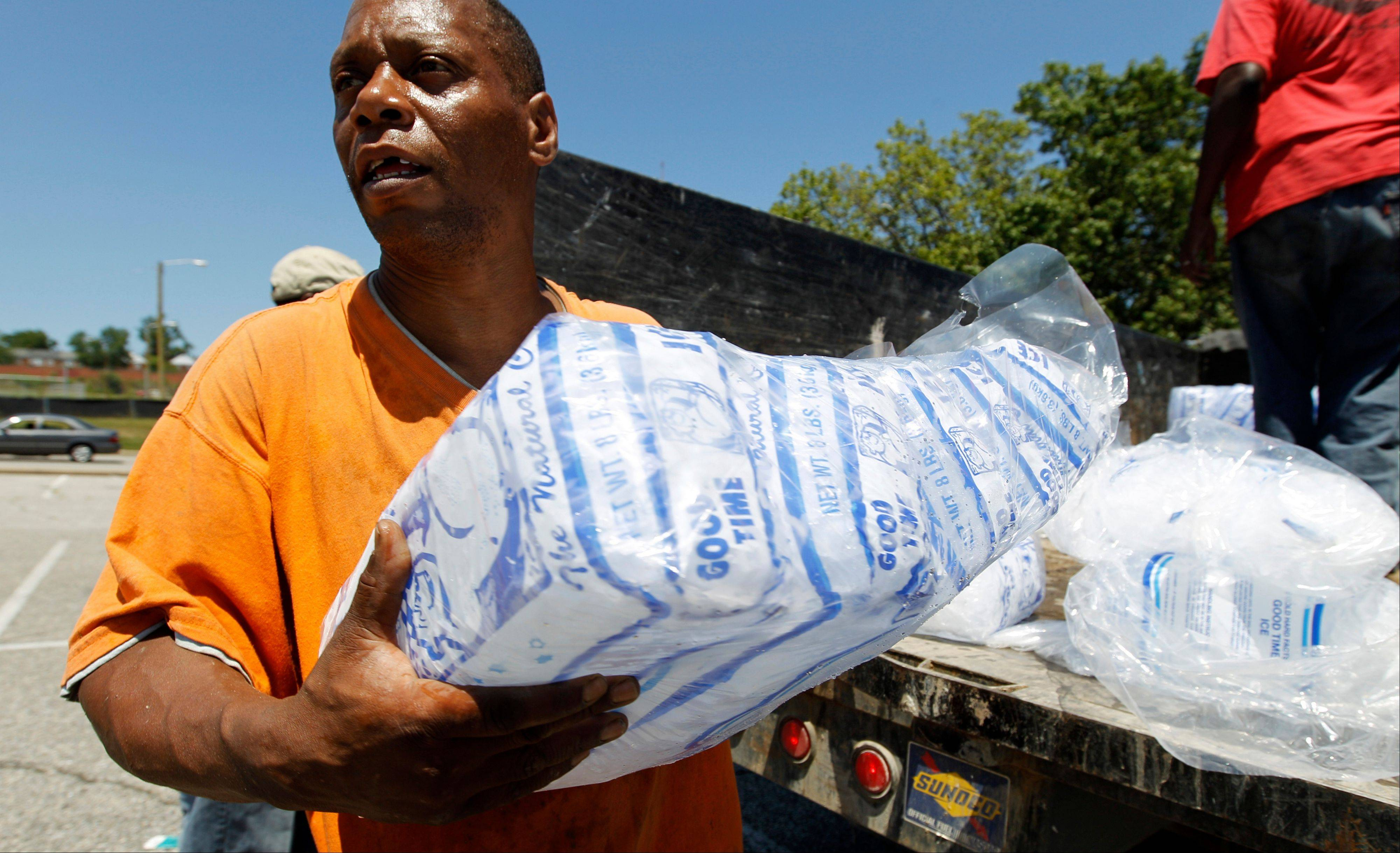 Baltimore city worker Joe Lane gives away free bags of ice to residents at the Northwood Plaza shopping center in Baltimore on Monday, July 2, 2012. Around 2 million customers from North Carolina to New Jersey and as far west as Illinois were without power Monday morning after a round of summer storms.