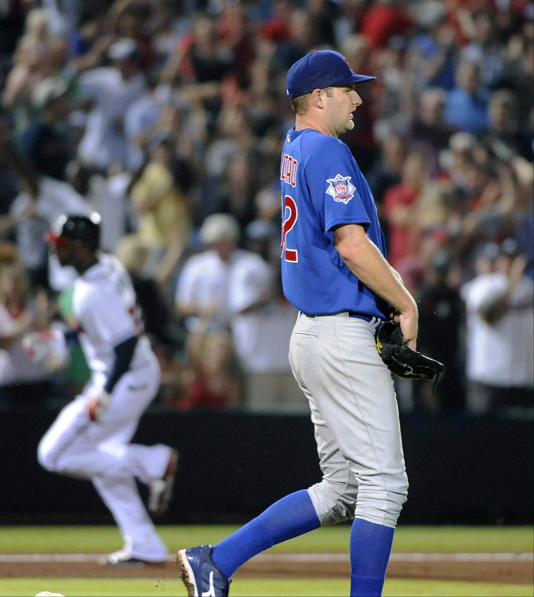 Cubs starting pitcher Chris Volstad walks near the mound Tuesday after giving up a home run to Atlanta Braves right fielder Jason Heyward, rear, who rounds third base during the fifth inning at Turner Field in Atlanta.