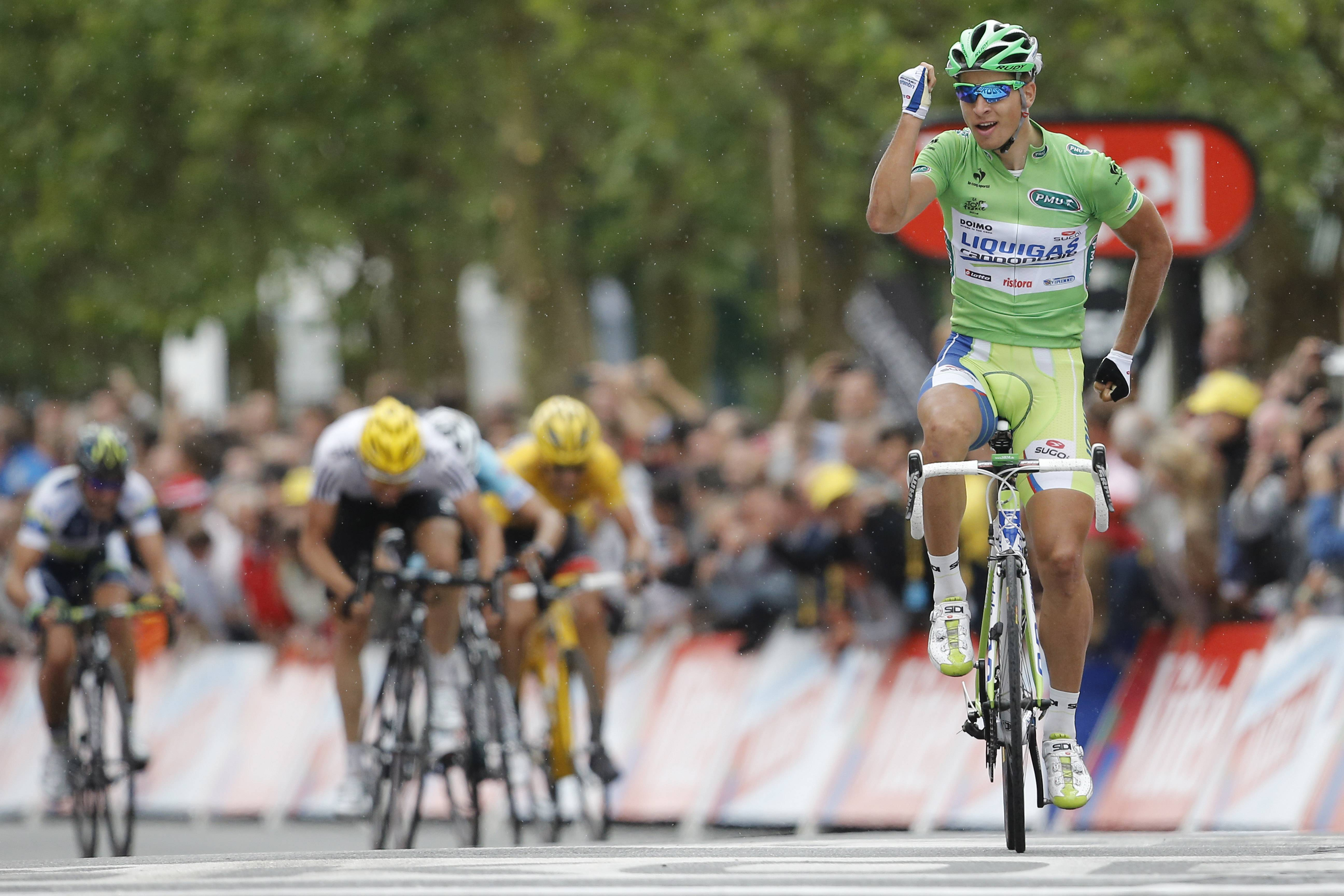 Peter Sagan celebrates Tuesday as he crosses the finish line ahead of Fabian Cancellara, wearing the overall leader's yellow jersey, second right, Peter Velits, third from right, and Edvald Boasson Hagen, second left, to win the third stage of the Tour de France cycling race over 122.4 miles.