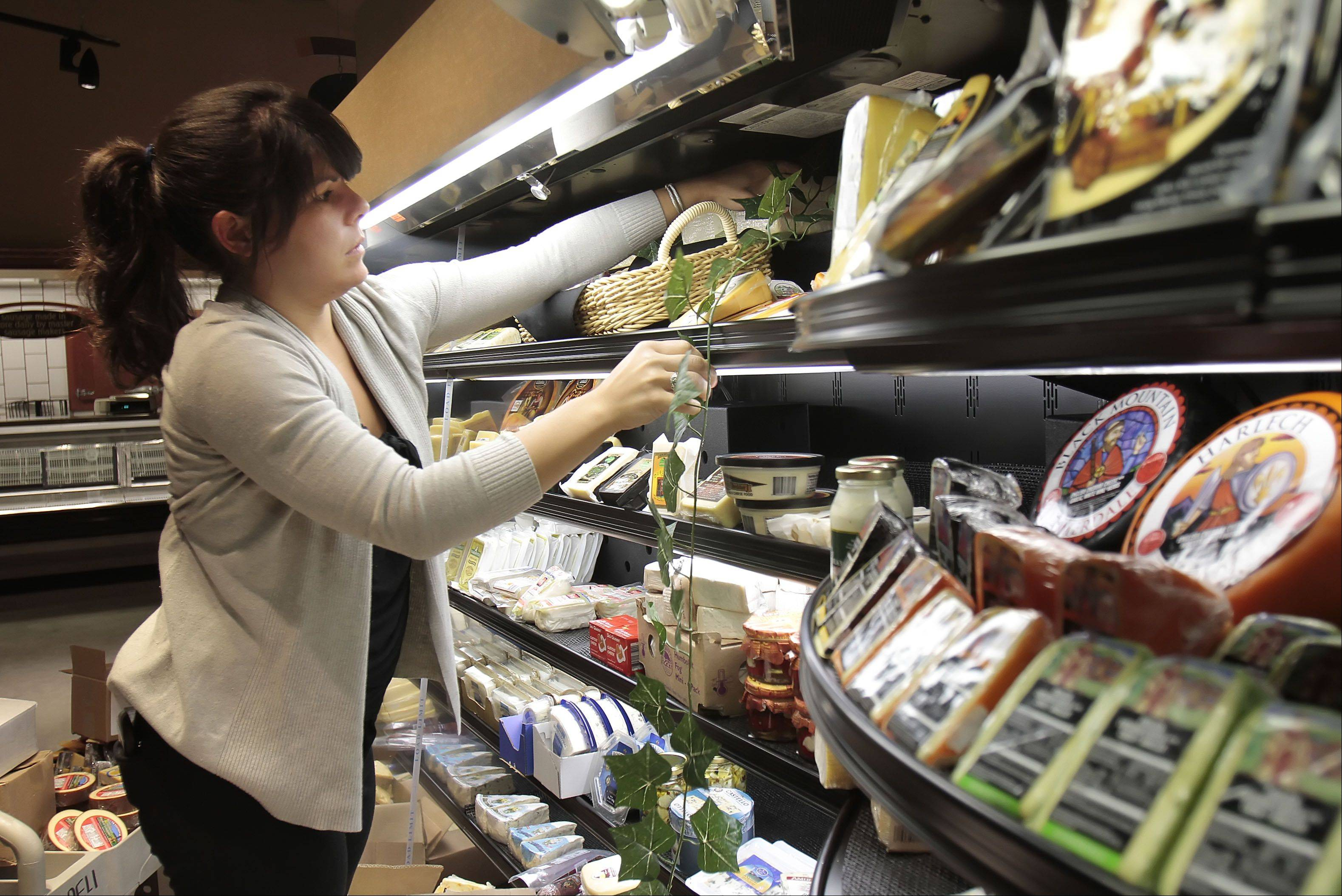 Mariah Colbert stocks the specialty cheese shelves at the Mariano's Fresh Market on Milwaukee Avenue in Vernon Hills.
