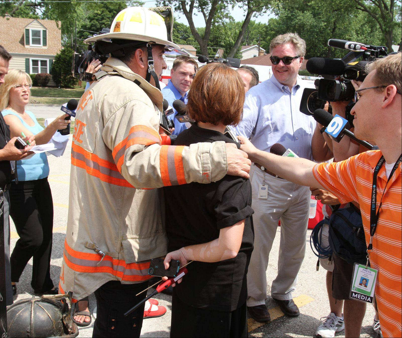 Michael Kuryla, president of Cook County Fire Chiefs Association consoles Laura Barros, assistant executive director at the Illinois Fire Safety Alliance in Mount Prospect, as she answers reporters' questions after being burned during a fireworks safety demonstration.