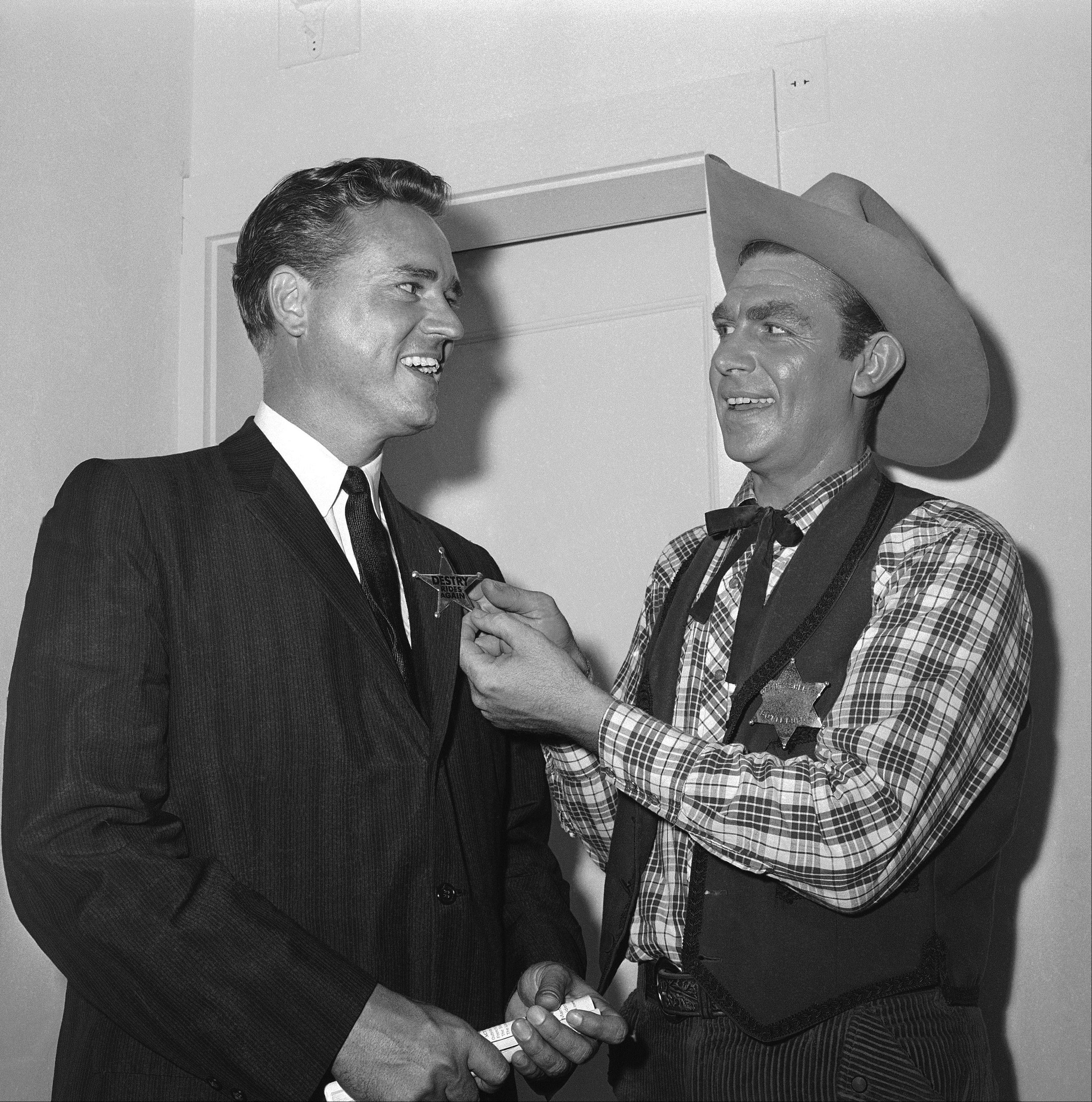 Andy Griffith, right, star of the Broadway musical? Destry Rides Again? and a native of North Carolina, pins a badge on the lapel of Ernest F. Hollings, governor of South Carolina, after performance at night on May 21, 1959 in the Imperial Theater, New York.