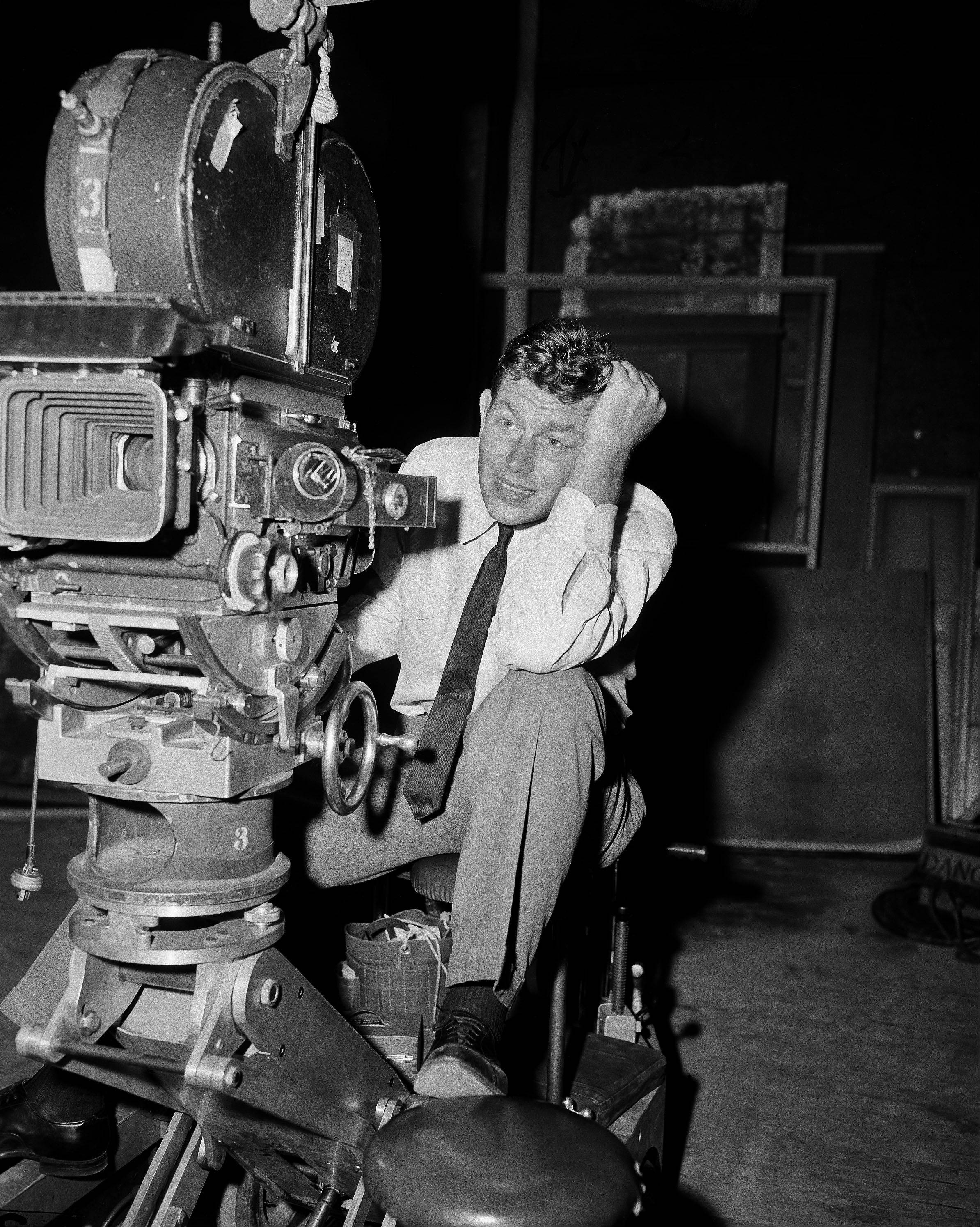 "Andy Griffith, star of the New York stage play ""No Time for Sergeants,"" ponders the problems of a cameraman at Warner Brother's studio in Burbank, Nov. 8, 1957 where he is working in ""Onionhead."" The movie is a story of a recruit in the U.S. Coast Guard, played by Griffith, who loses all his hair and is dubbed ""Onionhead"" by his crew mates."
