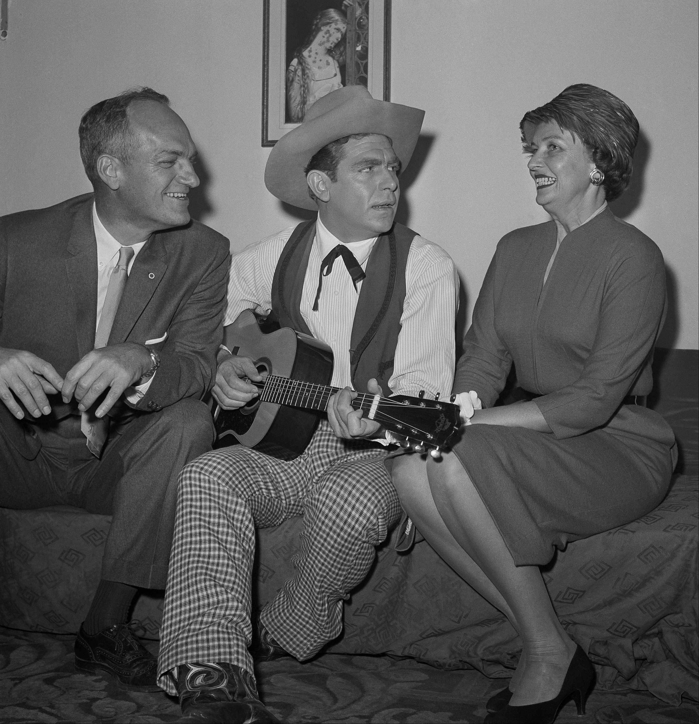 Mr. and Mrs. Nathaniel A. Carswell of Nashville listen to Andy Griffith, star of? Destry Rides Again,? as he plays guitar in his dressing room backstage at the Imperial Theater, Nov. 4, 1959 in New York.