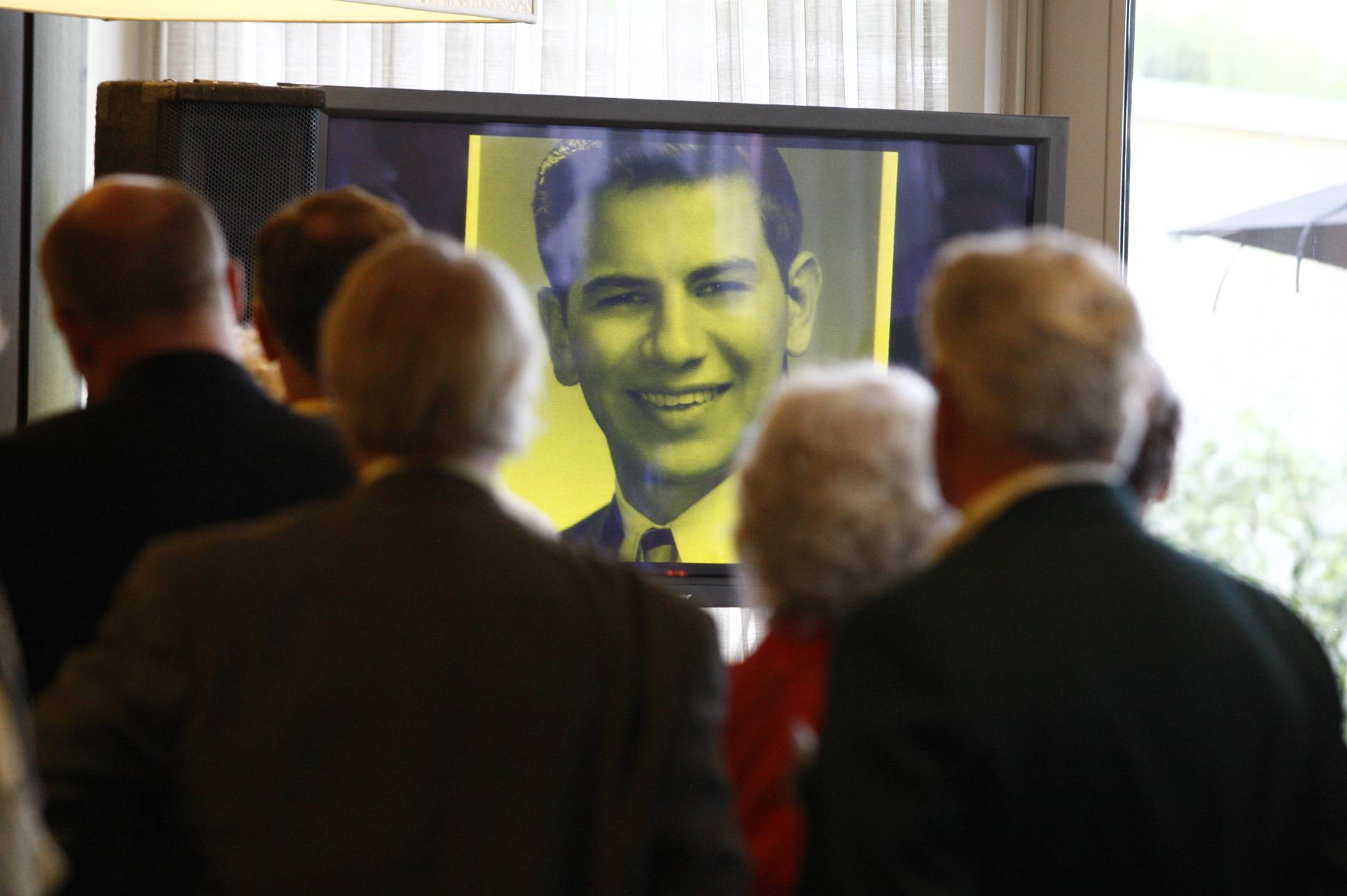 Caption: A video retrospective of Cleve Carney captivates the guests at the gala event celebrating Carney's life. (Press Photography Network/Special to College of DuPage)