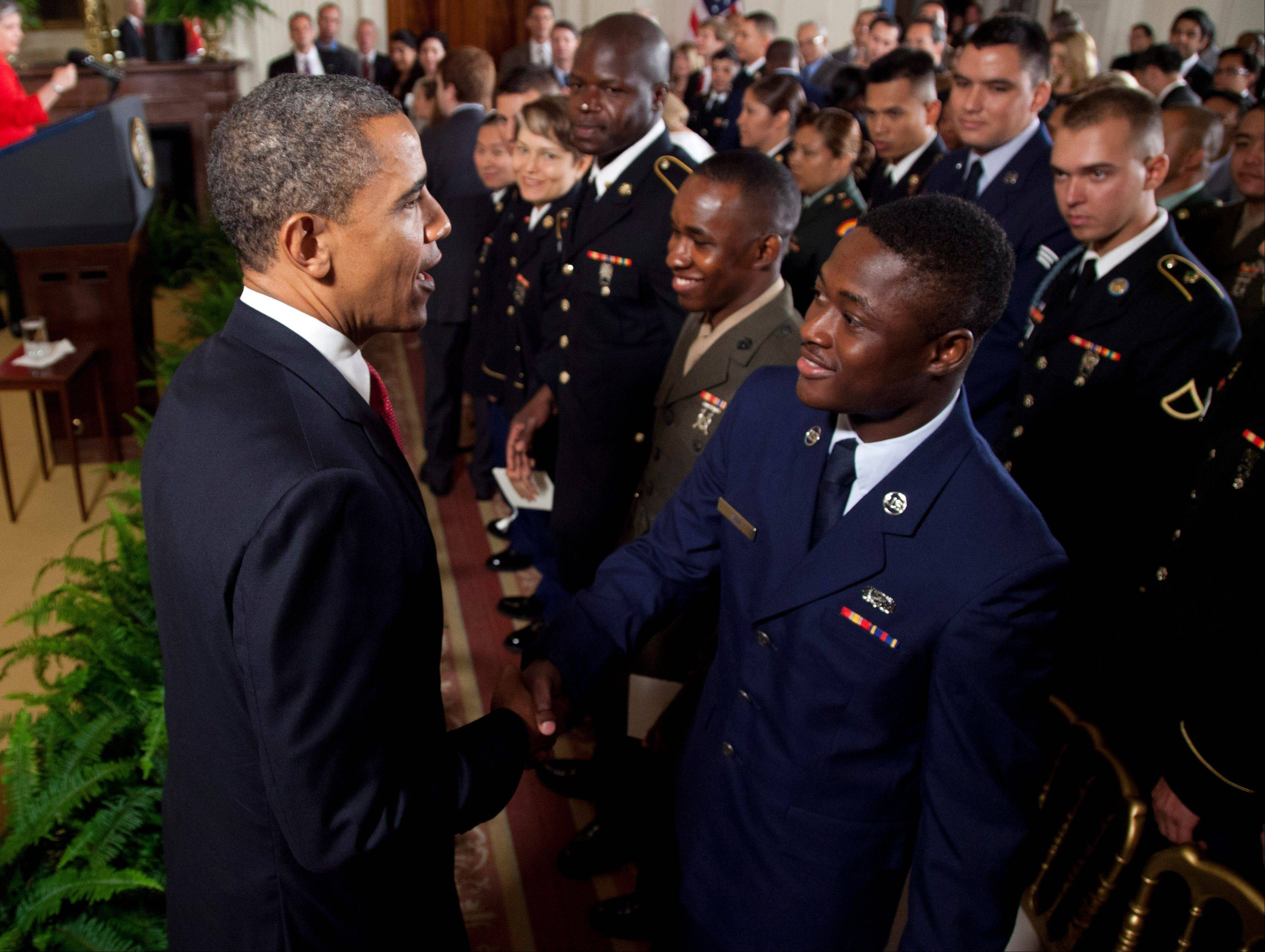 President Barack Obama greets service members after they became U.S. citizens during a naturalization ceremony in the East Room of the White House on Wednesday.