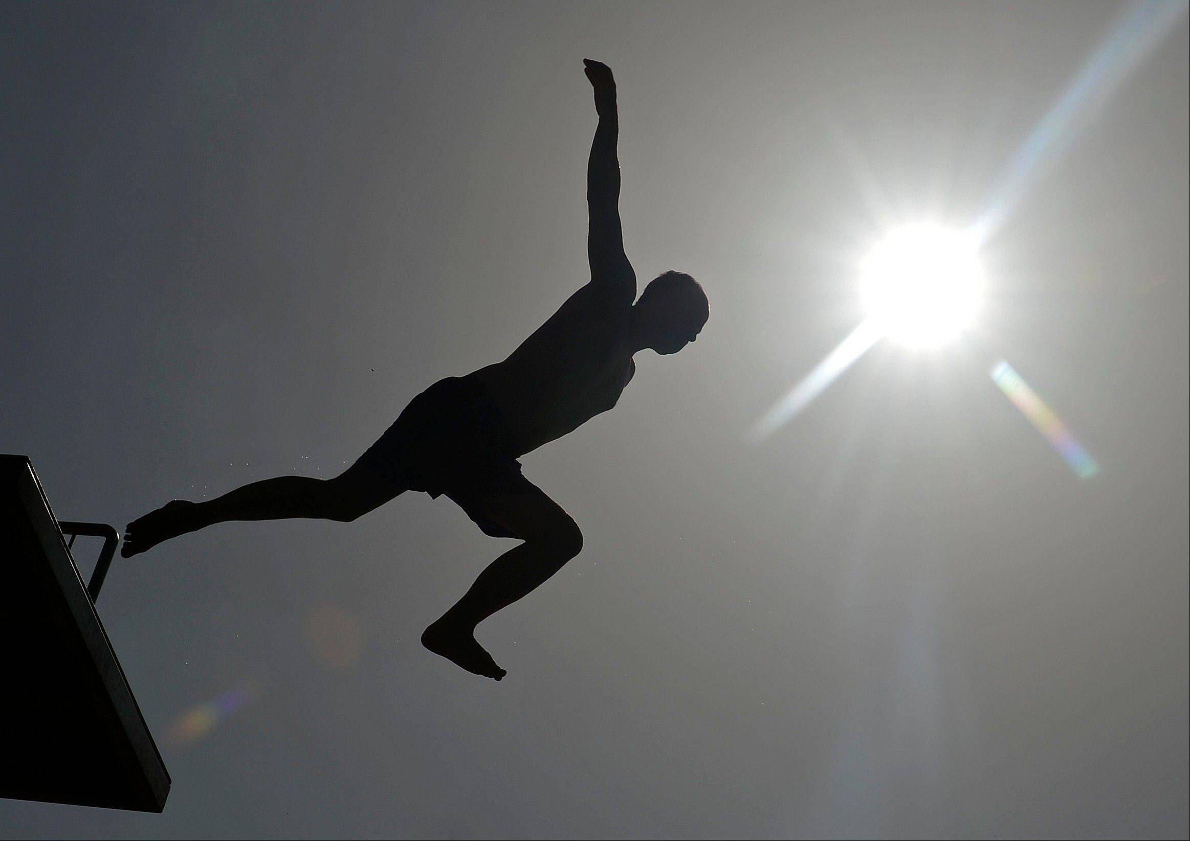 A man dives from a pool tower in the open air pool Nordbad in Erfurt, Germany, last weekend. The heat wave there is over, but we in the suburbs are not done yet.