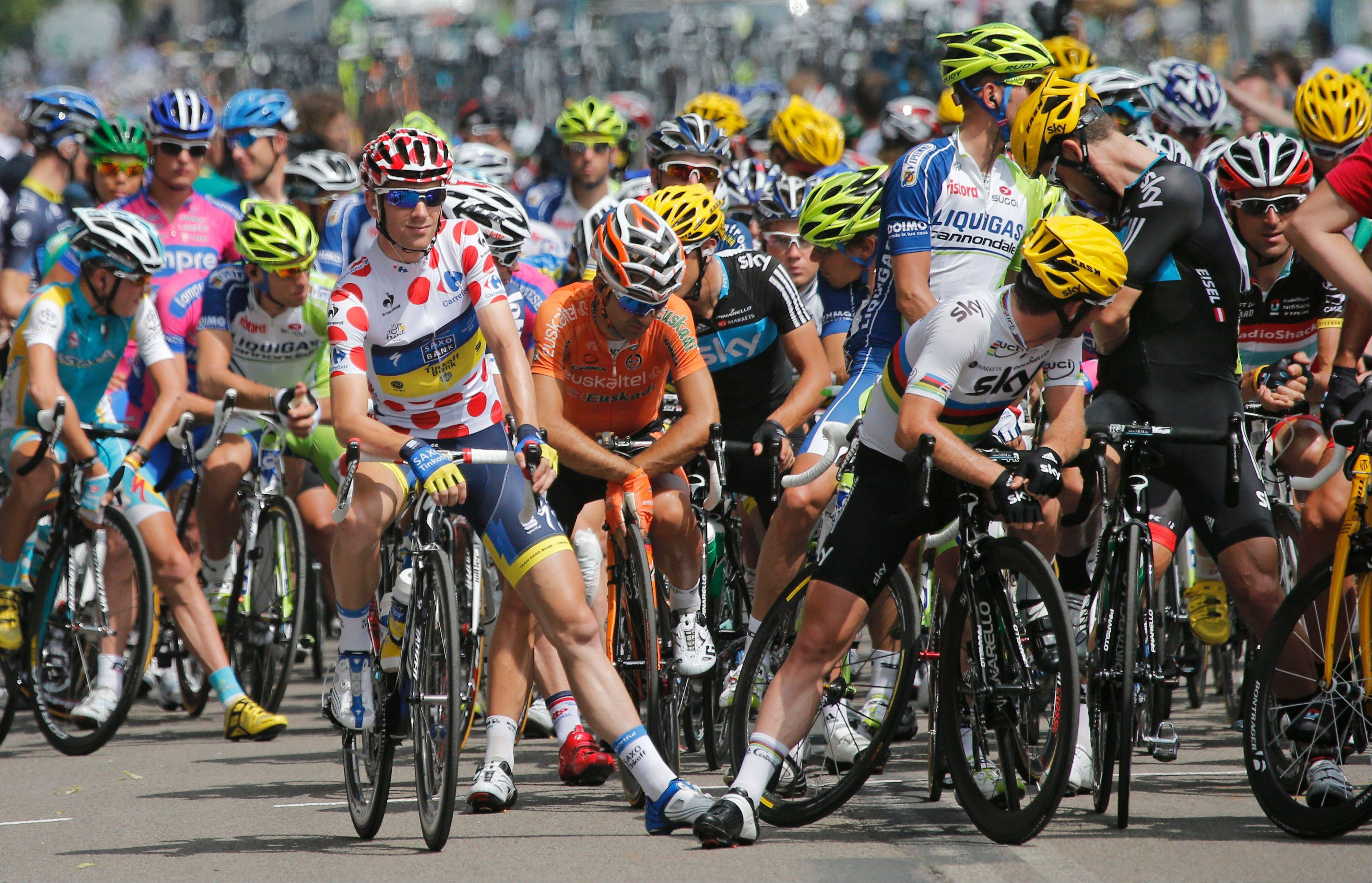 Michael Morkov of Denmark, wearing the best climber�s dotted jersey, left, and Mark Cavendish of Britain, front right in rainbow jersey, wait with other riders for the start of the fourth stage of the Tour de France cycling race over 214.5 kilometers (133.3 miles) with start in Abbeville and finish in Rouen, France, Wednesday July 4, 2012.