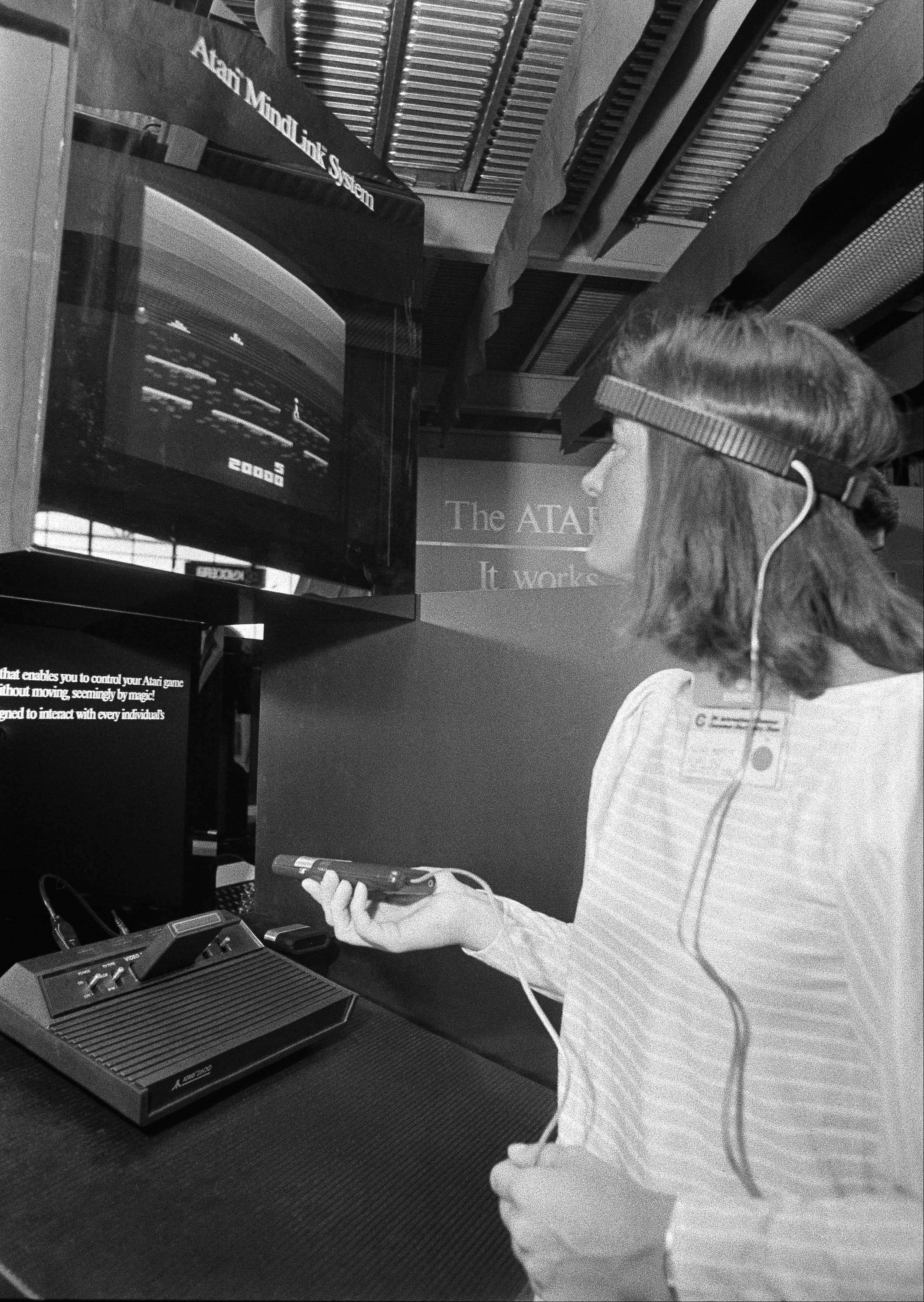 In this June 5, 1984, file photo, a woman in Chicago demonstrates Atari's new game, Mind Link, which utilizes a headband that picks up electrical impulse from the movement of the forehead and transmits them to a receiver attached to a video game or home computer console.