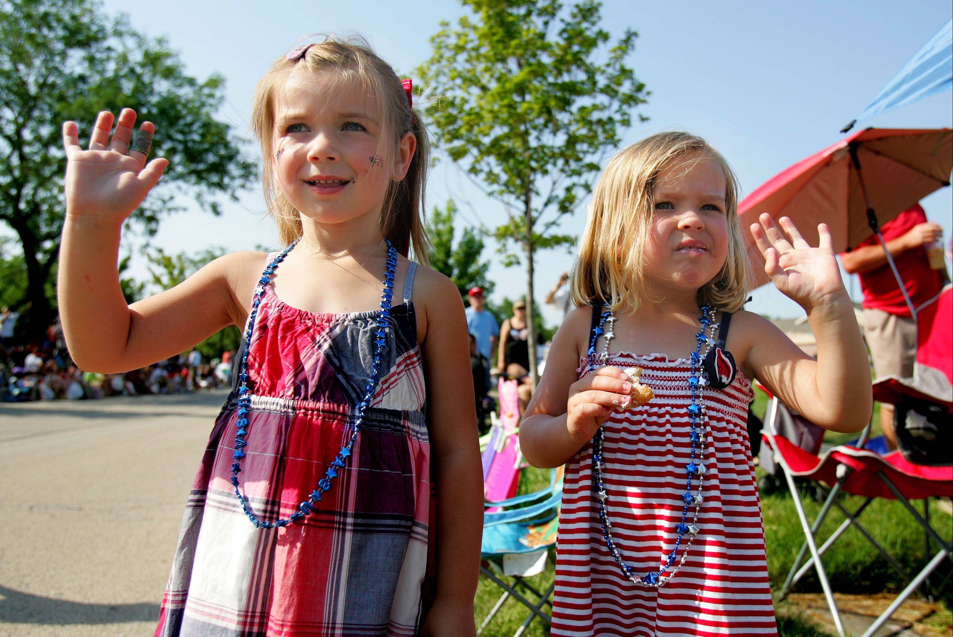 Four-year-old Maddy Gardner, left, and 3-year-old Olivia Altergott, both of Wauconda, wave as the Vernon Hills Fourth of July Parade begins Wednesday morning.