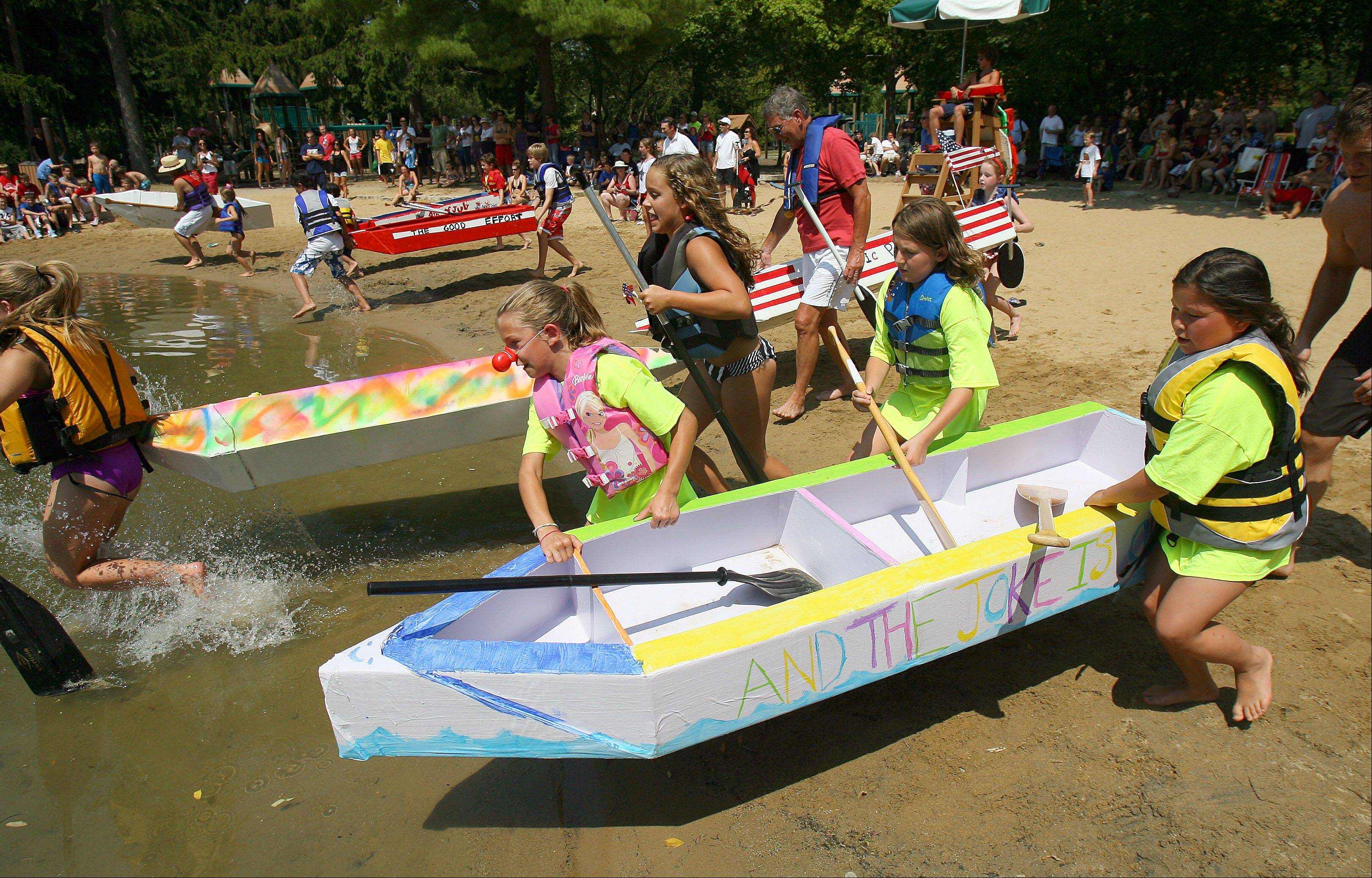 Racers dash for the water during a cardboard boat regatta at Lincolnshire's Red White and Boom 2012 event Wedensday at Spring Lake Park.