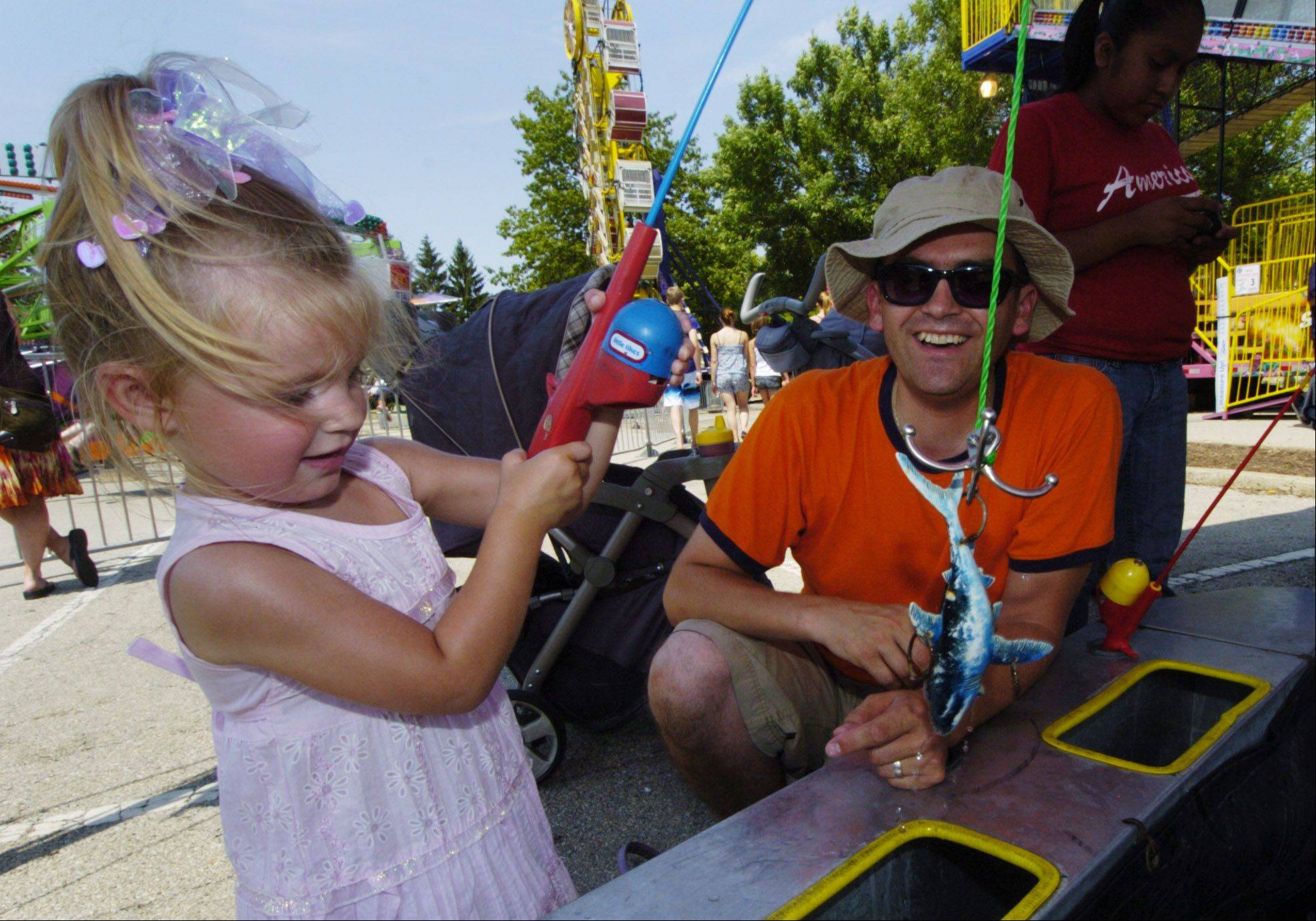 Karolina Sen, 2�, of Palatine catches a toy shark with the help of her dad, Piotr, during the Palatine Jaycees Hometown Fest.