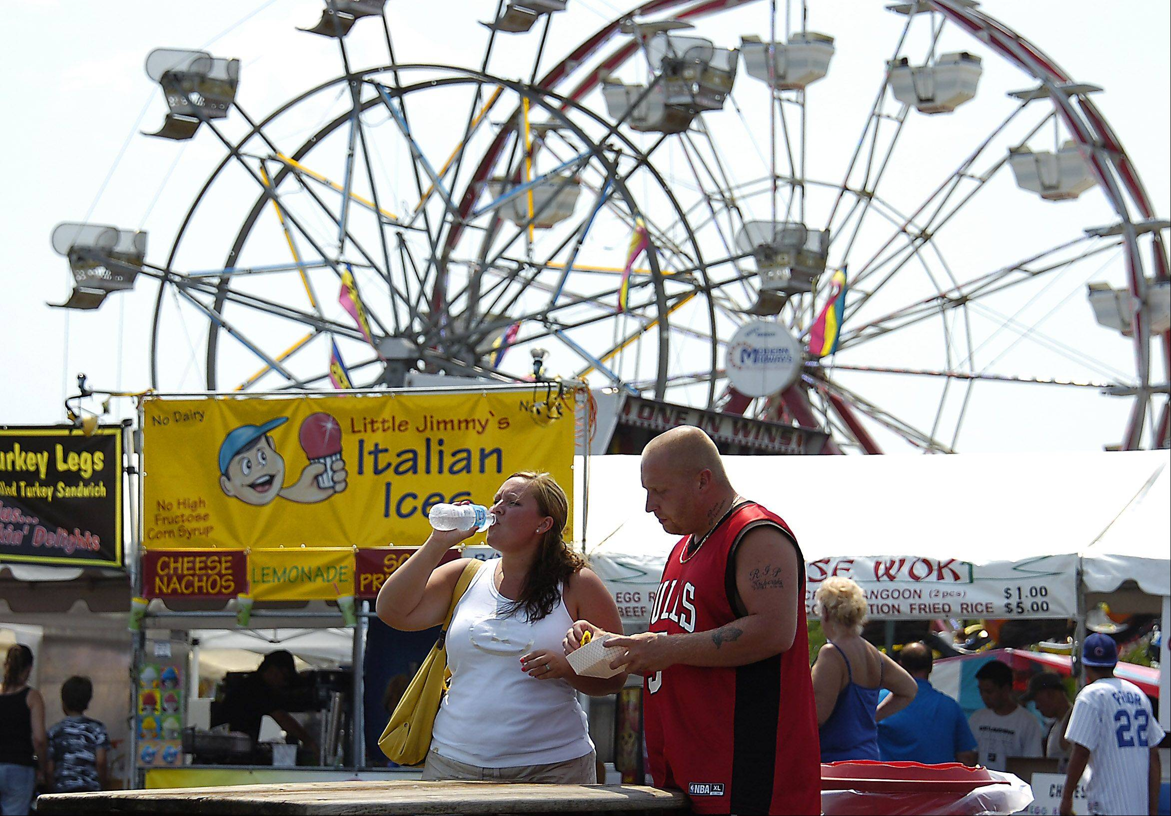 Against a background of ferris wheels Marina McKay gets cool with water while Cruz Rodriguez samples an empanada during the extreme heat at the Northwest Fourth-Fest at the Sears Centre in Hoffman Estates.