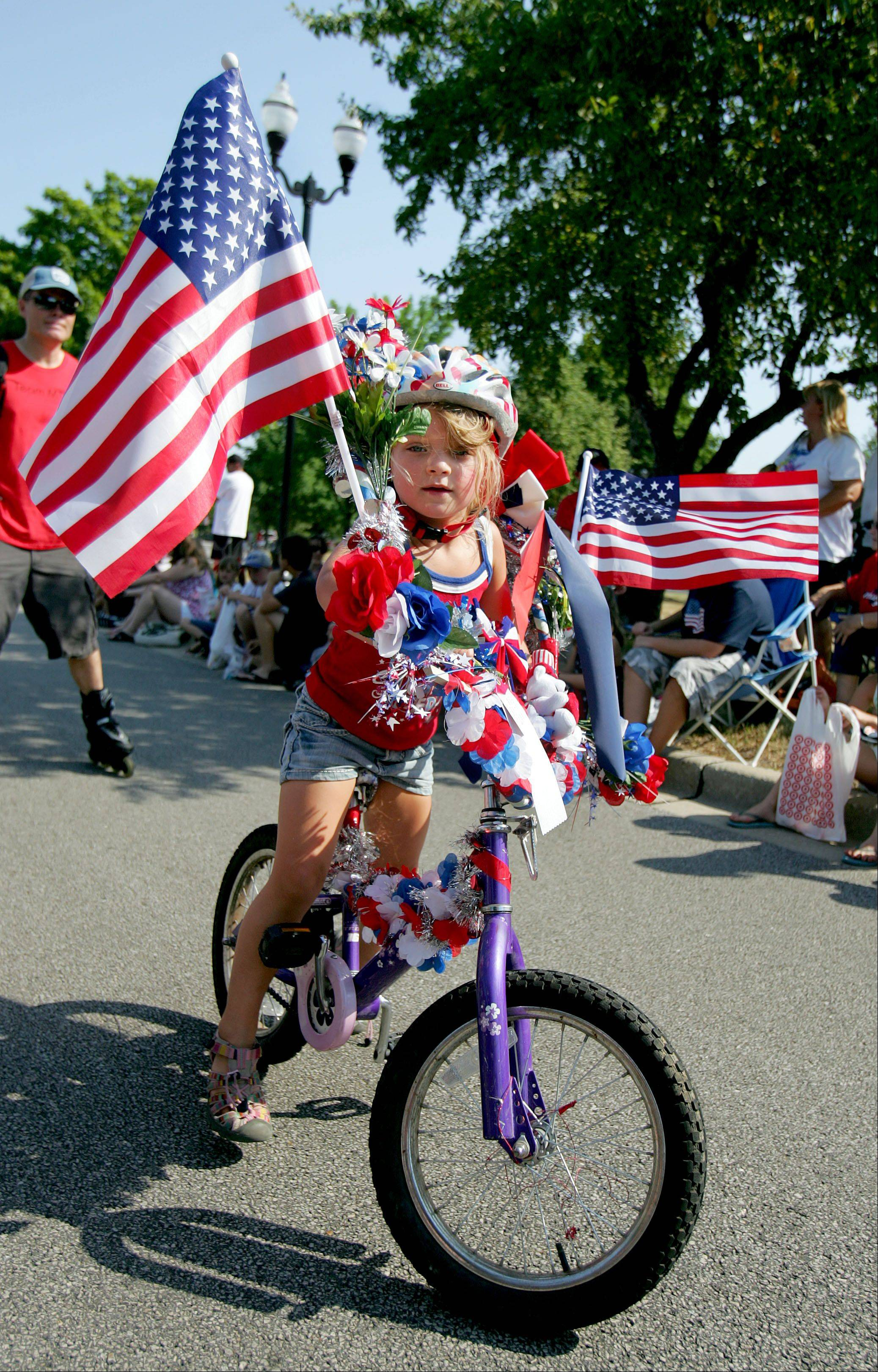 Five-year-old Clara Sheridan of Vernon Hills shows off her decorated bike as she participates in the Vernon Hills Fourth of July Parade Wednesday morning.