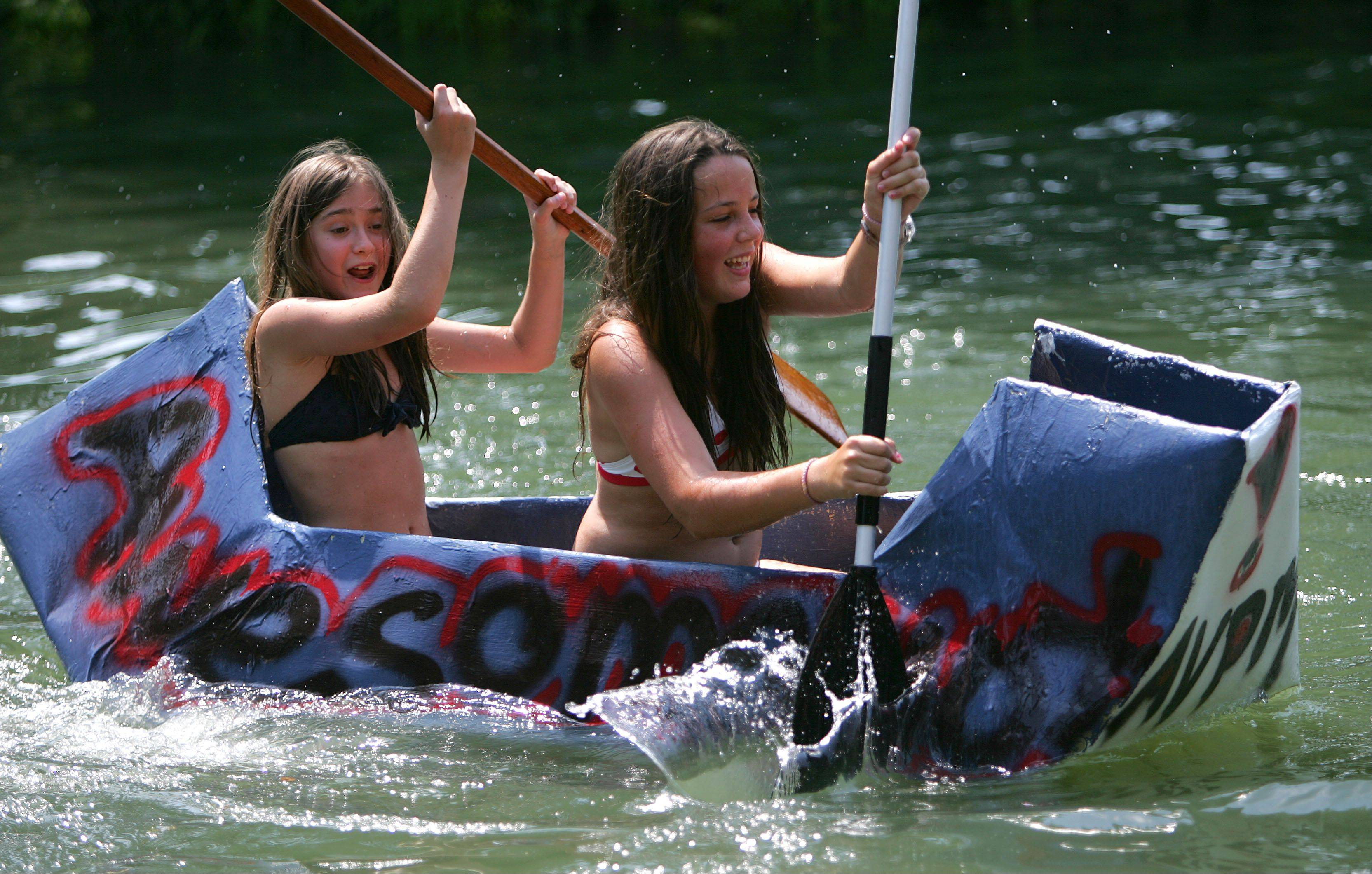 12-year-old Sahsa Pinchuk, left, and 14-year-old Naomie Lapointe, both of Lincolnshire compete in a cardboard boat regatta as Lincolnshire held their Red White and Boom 2012 event on Wednesday at Spring Lake Park.