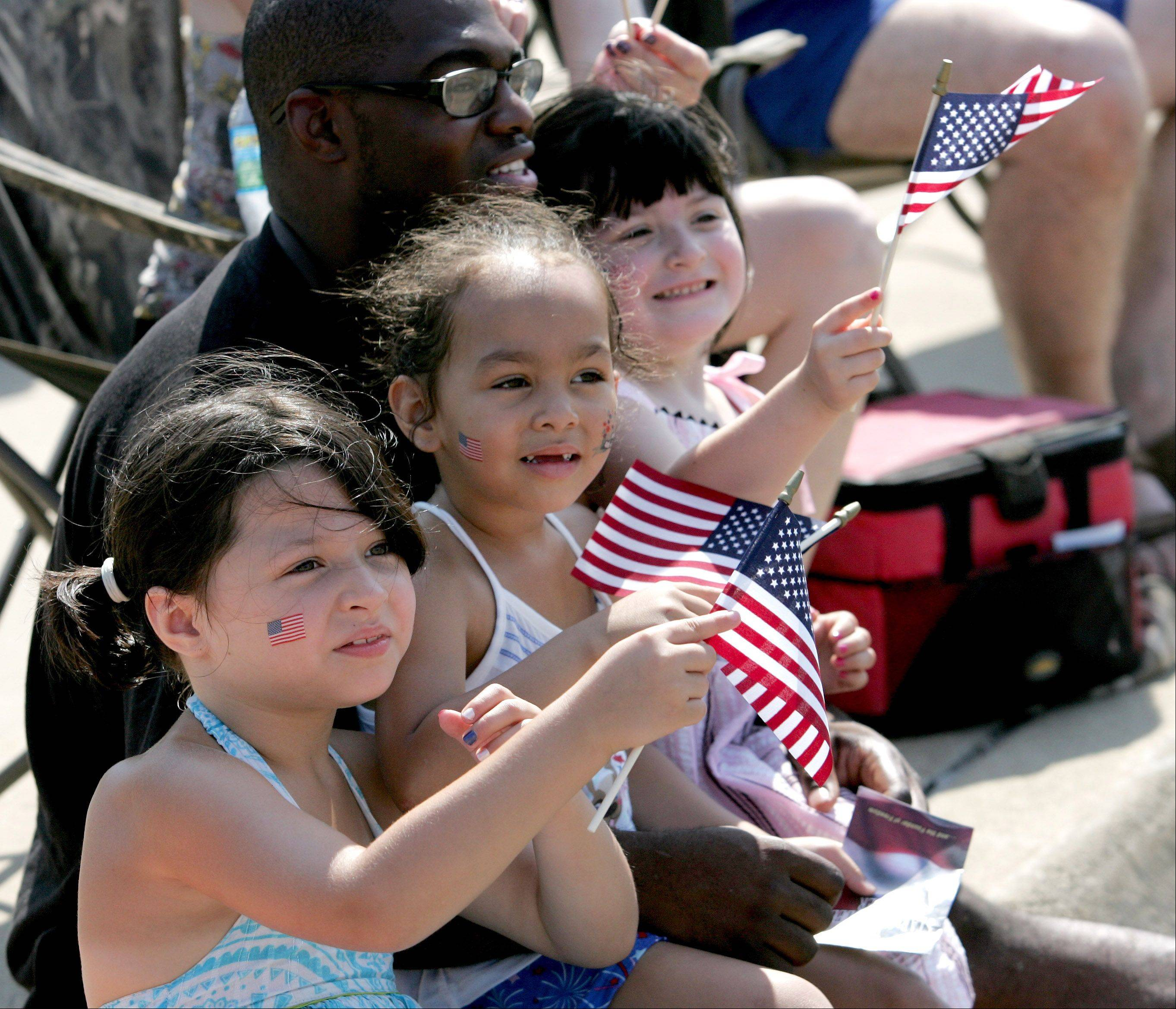 Left to right are cousins Izabella Nelson-Carrillo, 6, Cailyn Nelson-Teague, 4 and Alaina Nelson-Carrillo, 4, with Charles Teague of Aurora enjoying the 4th of July parade in Aurora on Wednesday.