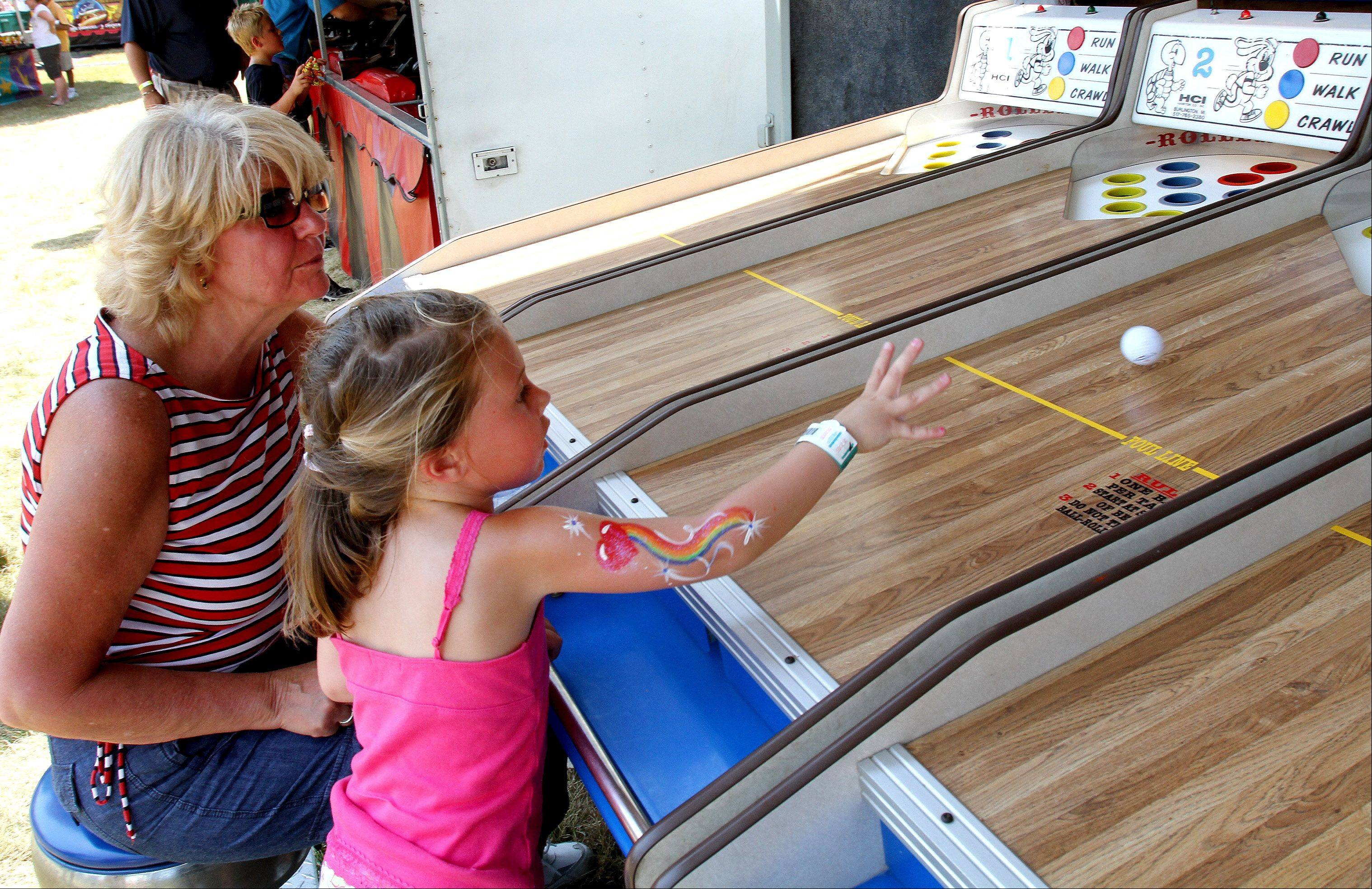 Madison Turek, 4 of Lombard, plays the Derby Race game with her grandma Irene Turek at the Taste of Lombard on Wednesday.