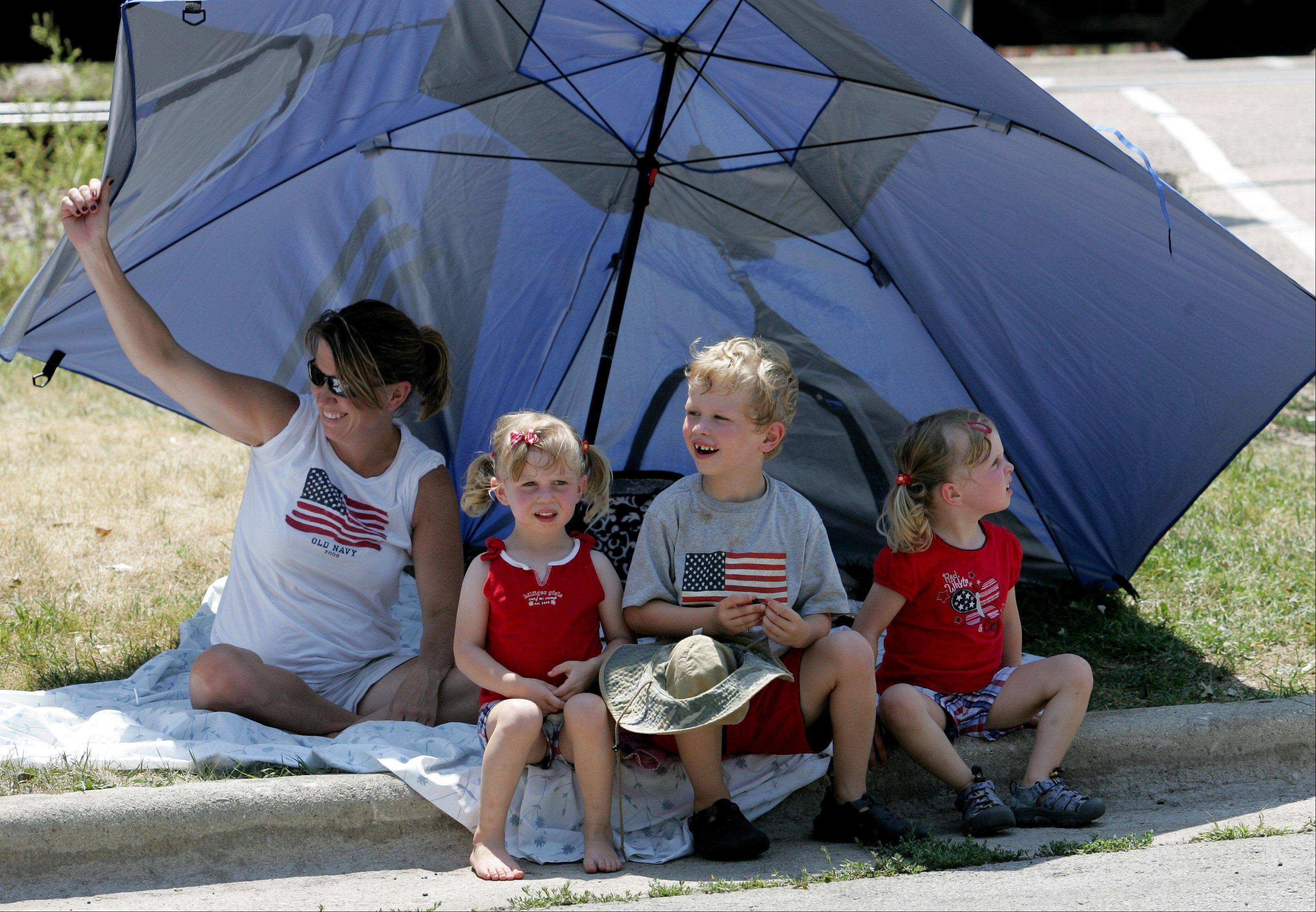 Janet Alman of Wheaton uses a big umbrella for shade while watching the 4th of July parade in Glen Ellyn on Wednesday with her kids, left to right, Sarah, 3, Jacob, 6 and Ashley, 3.