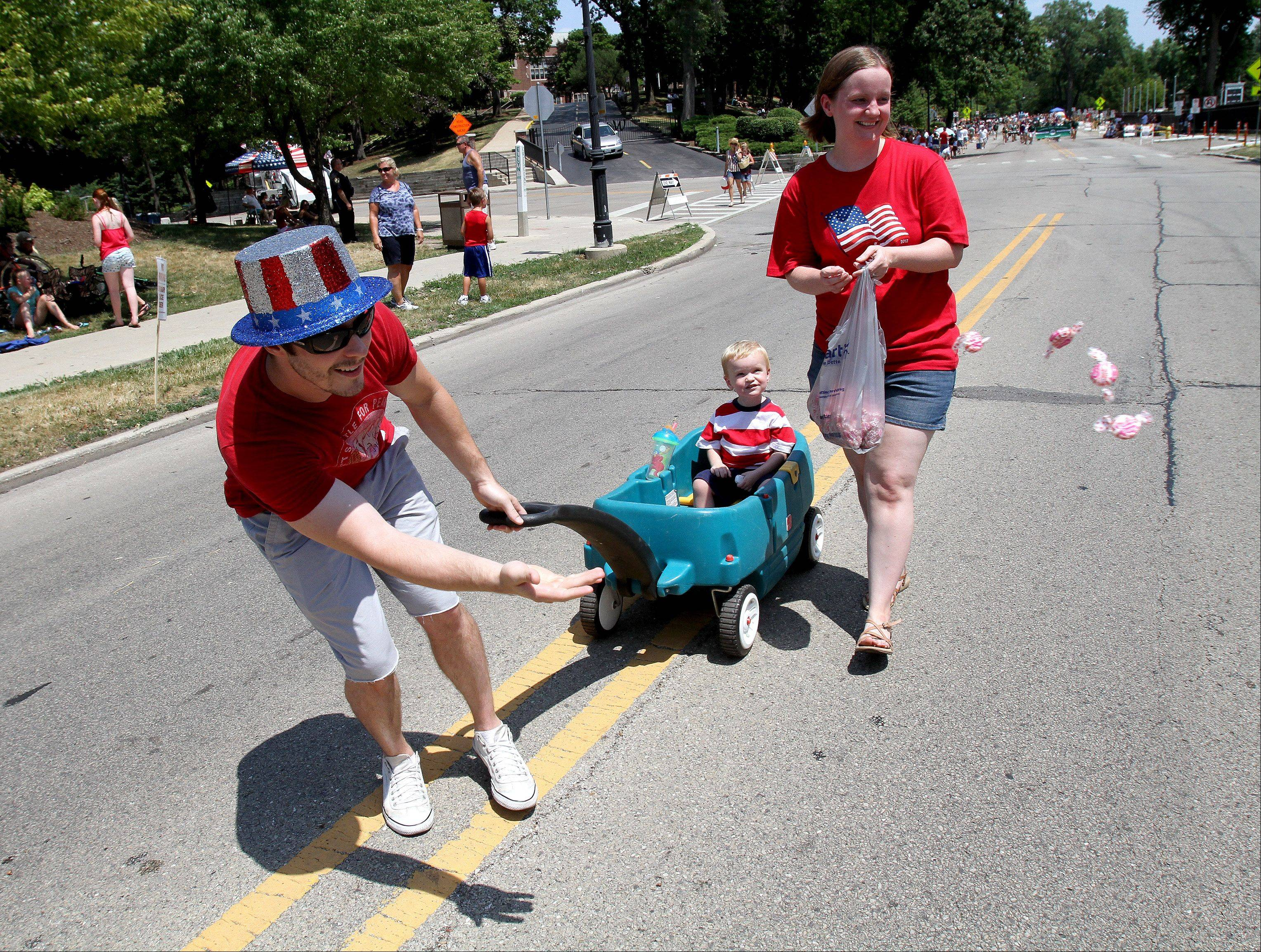 Michael Chrissy from Gigi's Playhouse throws out some candy as he and Erin Gunsteen with Emmett Gunsteen, 2, take part in the 4th of July parade in Glen Ellyn on Wednesday.