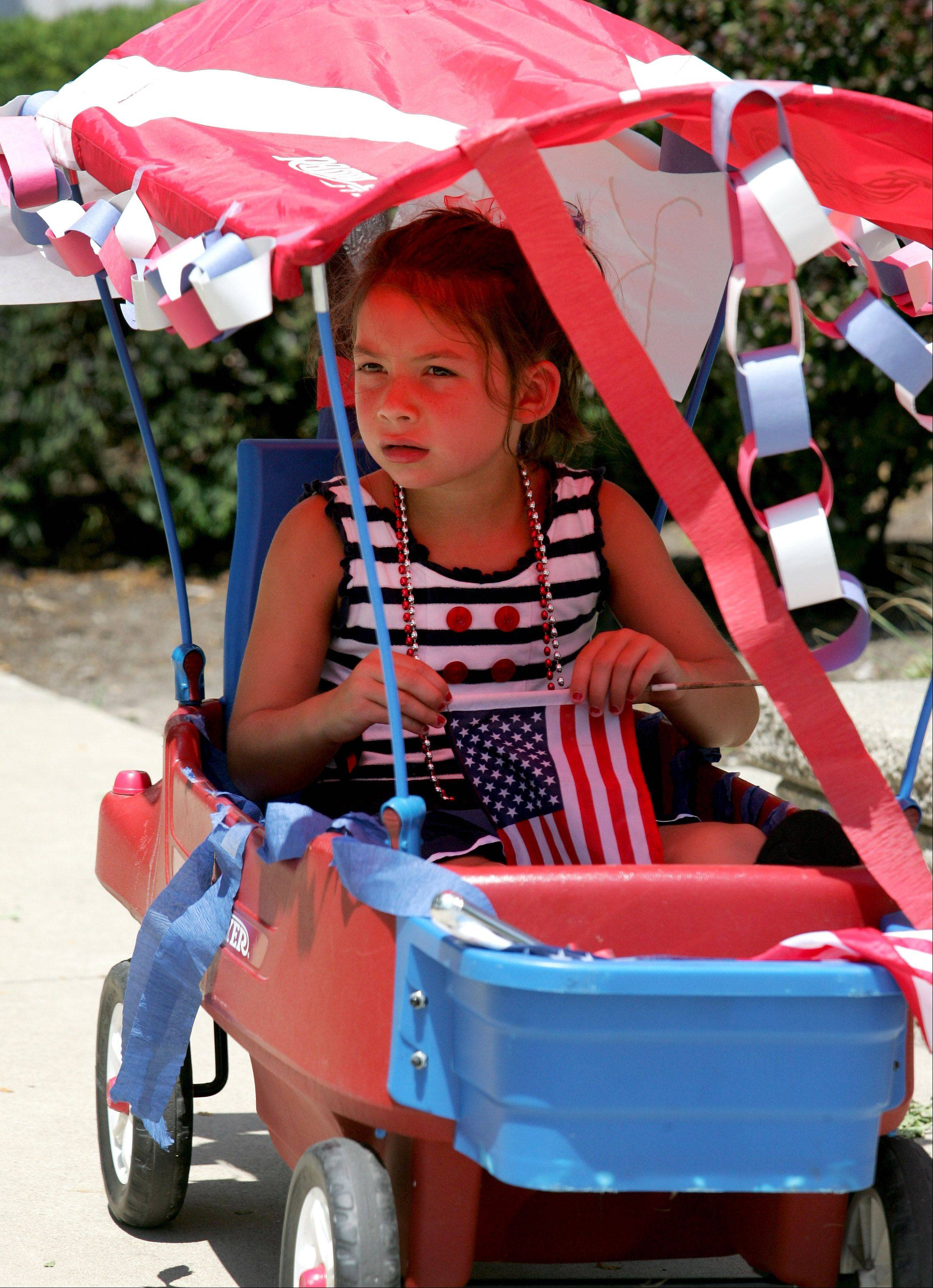 Natalie Snow, 7, of Wheaton, gets a shady spot in her wagon to watch the 4th of July parade in Glen Ellyn on Wednesday.