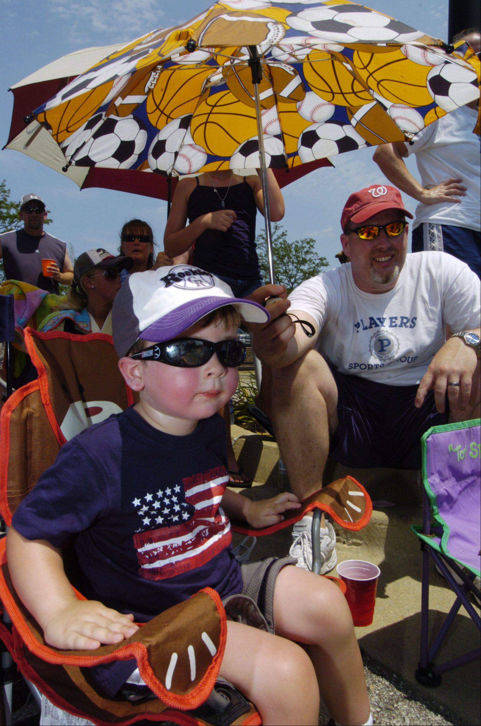 Jason Wendt of Arlington Heights shades is son, Lucas, 2, with an umbrella as the watch the Mount Prospect Fourth of July parade Wednesday.