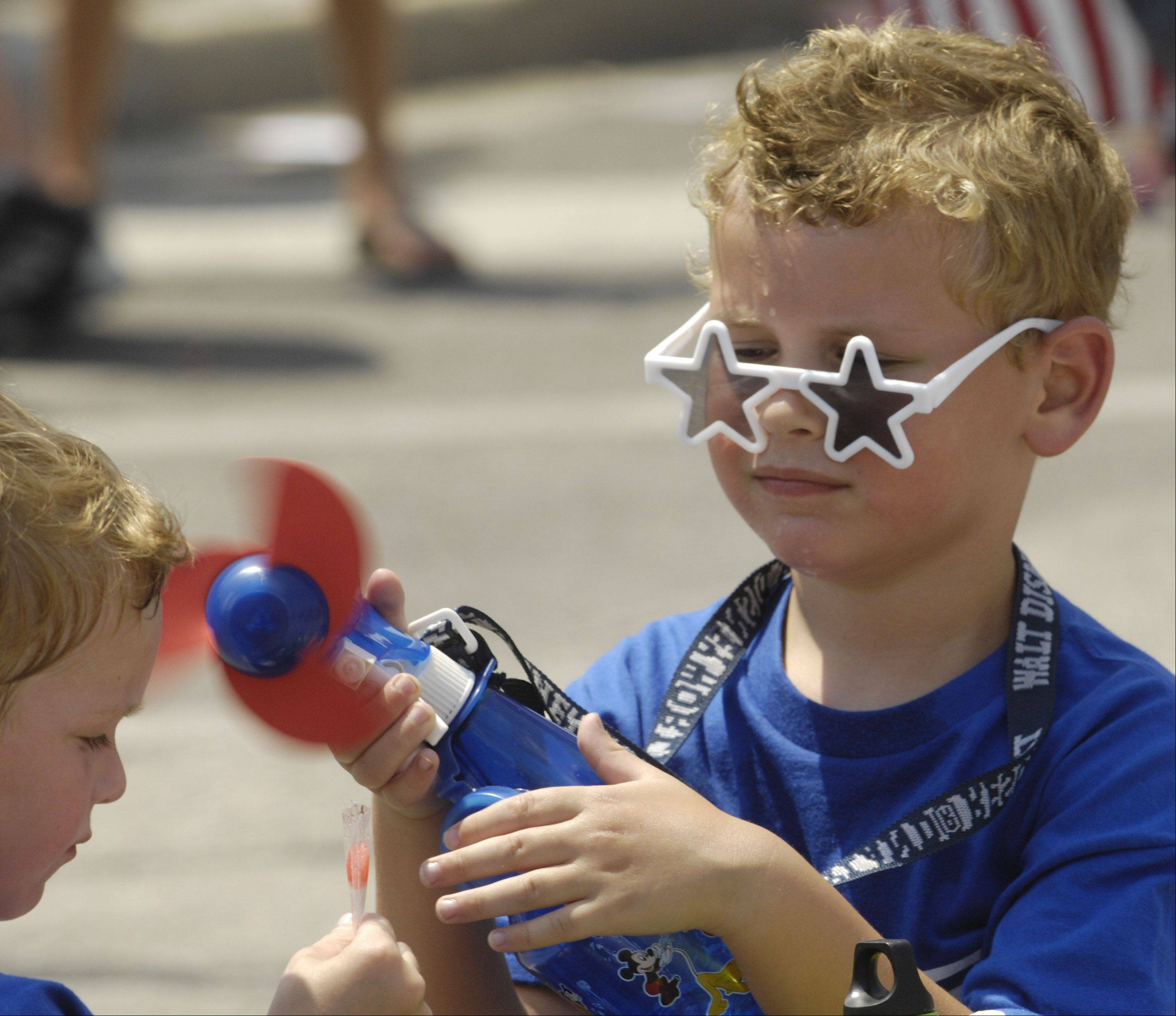 Jack Fitzgerald, 5, of Mount Prospect, aims a fan at his cousin, Tyler Fitzgerald, 3, of Schaumburg, as he helps him cool off during the Mount Prospect Fourth of July parade Wednesday.