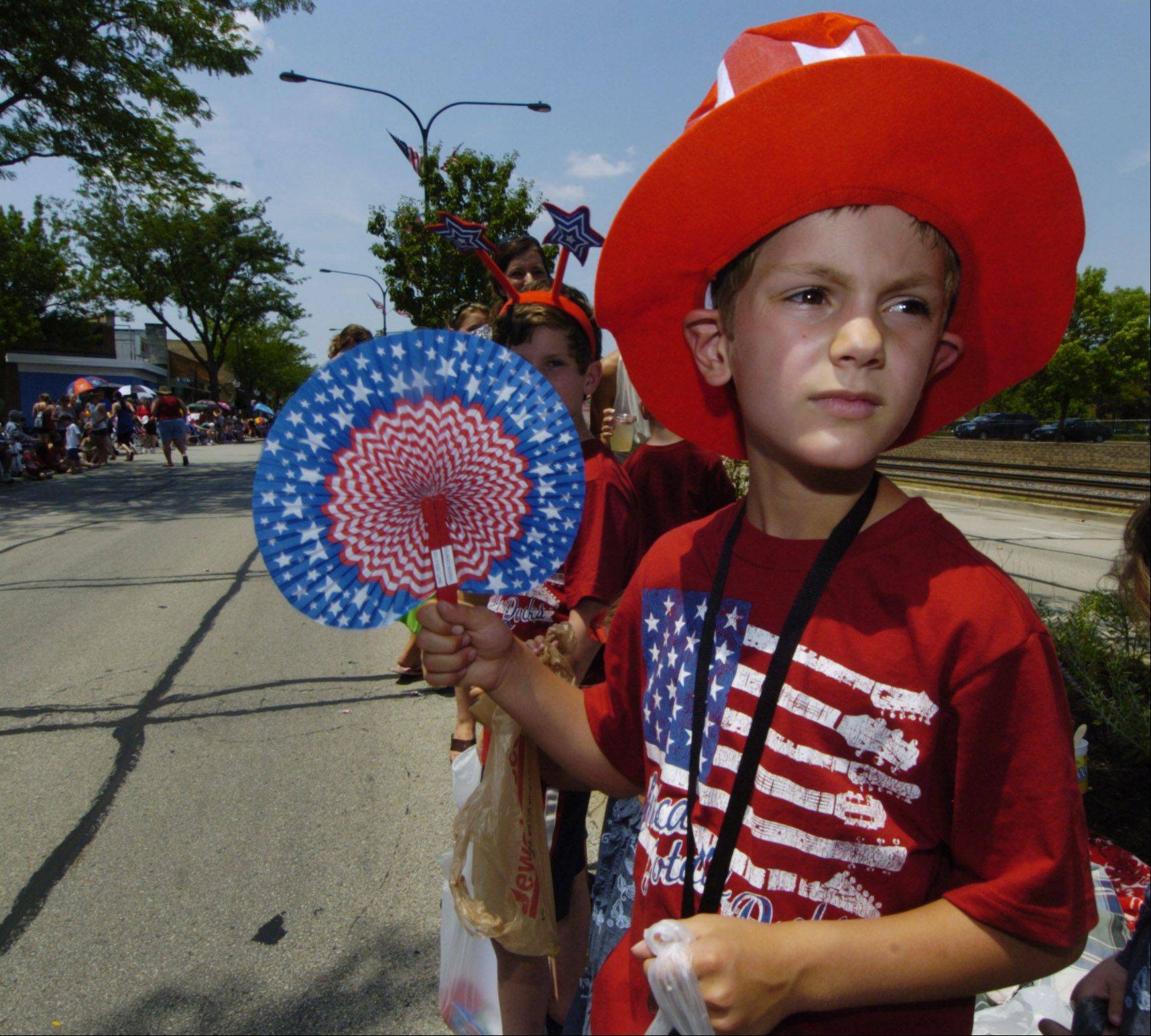 Jack Morman, 7, originally of Mount Prospect and now living in Denver, fans himself while waiting for the arrival of the next parade group during the Mount Prospect Fourth of July parade Wednesday. He comes back every year to watch the parade and visit family.