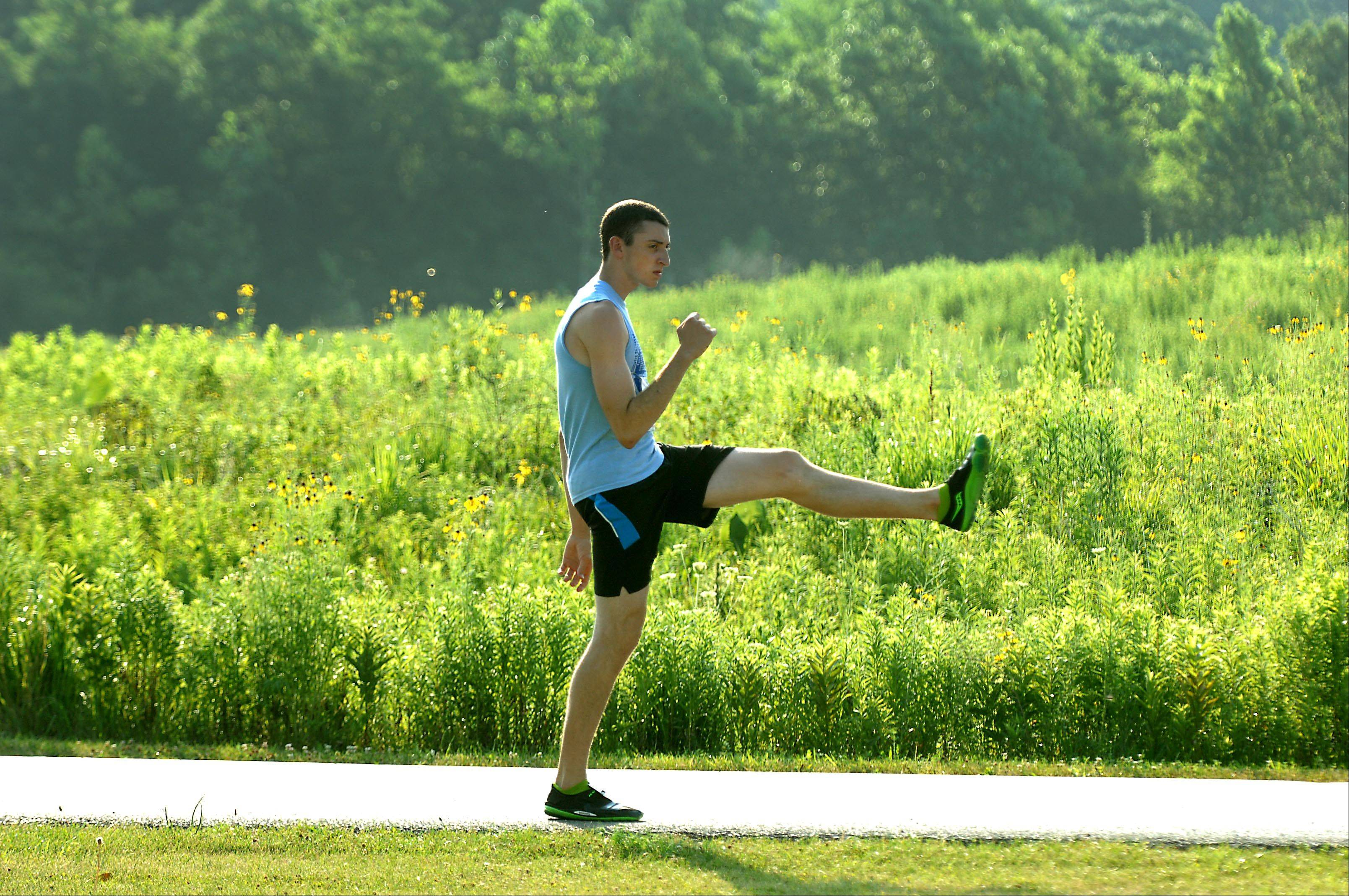 Dan Morgan, a senior at Burlington Central High School, stretches Wednesday before the start of The Great Western Freedom 4 road race at LeRoy Oakes Forest Preserve in St. Charles. He said his goal was only to have fun.