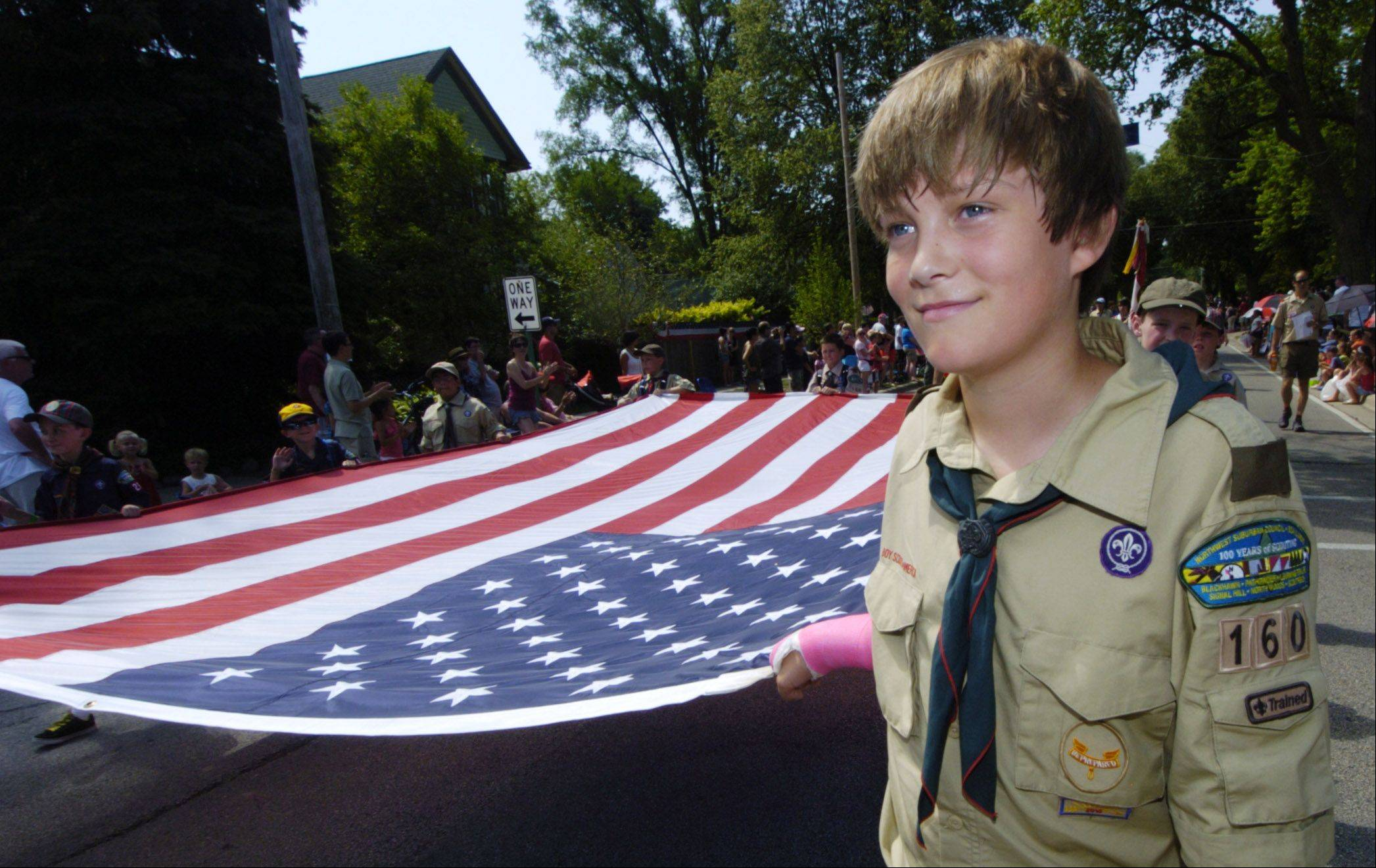 Philip Holzer, 13, helps carry the American Flag while marching with Boy Scout Troop 160 during the Des Plaines Fourth of July parade Wednesday.