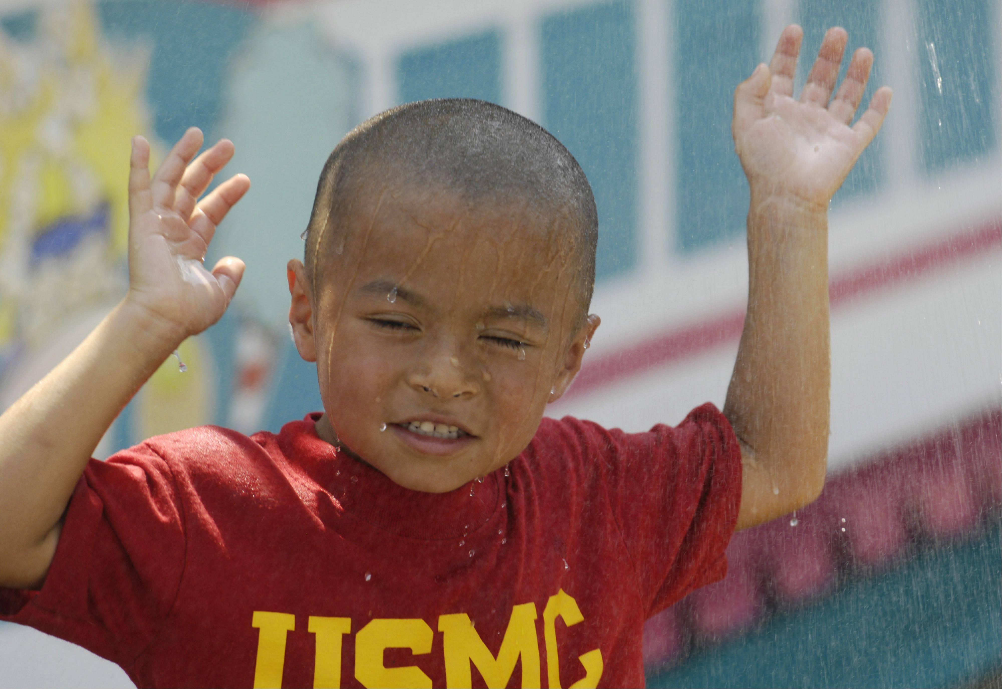 Aiden Yang, 5, of Palatine takes advantage of the spray of a cooling station during the Palatine Jaycees Hometown Fest Wednesday.