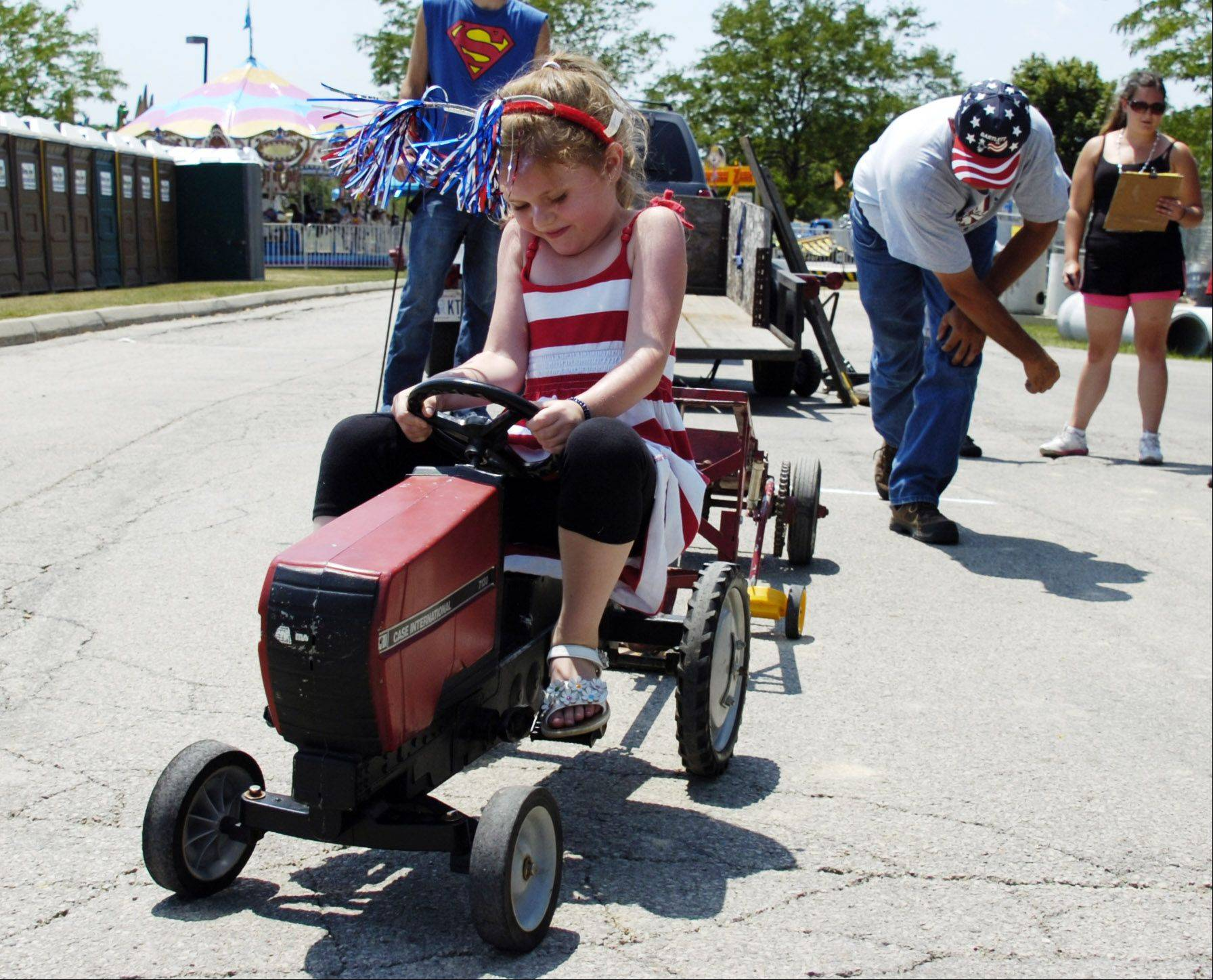 Emily Fagan, 5, of Bartlett in the extreme heat competes in the 40 lb weight division class tractor pull at the Bartlett Fourth of July festival on Wednesday.