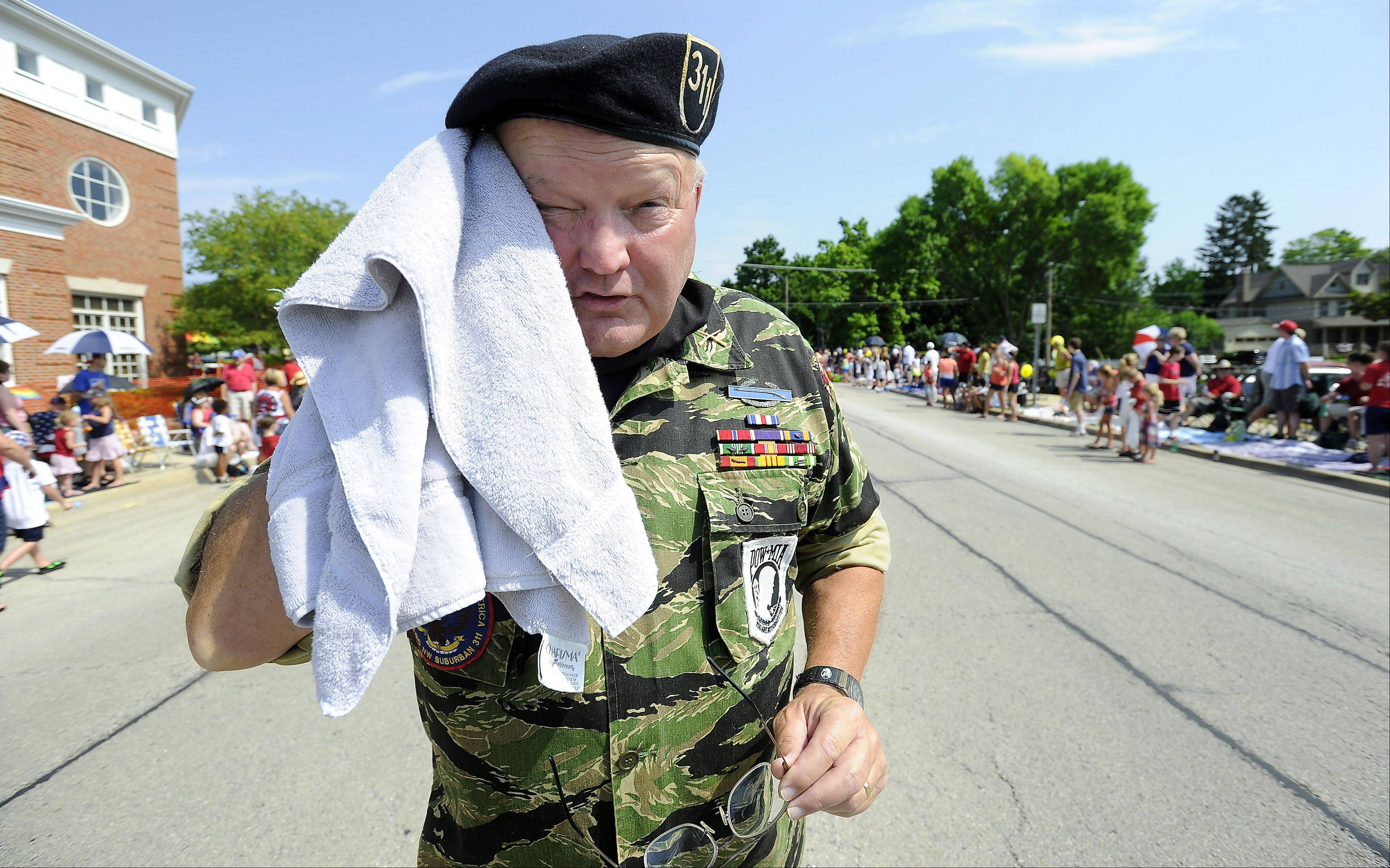 Bill Christiansen of Des Plaines Vietnam Veterans of America Chapter 311 taking a moment to wipe down his sweaty head while marching in a very hot Fourth of July the parade on Wednesday in Arlington Heights.