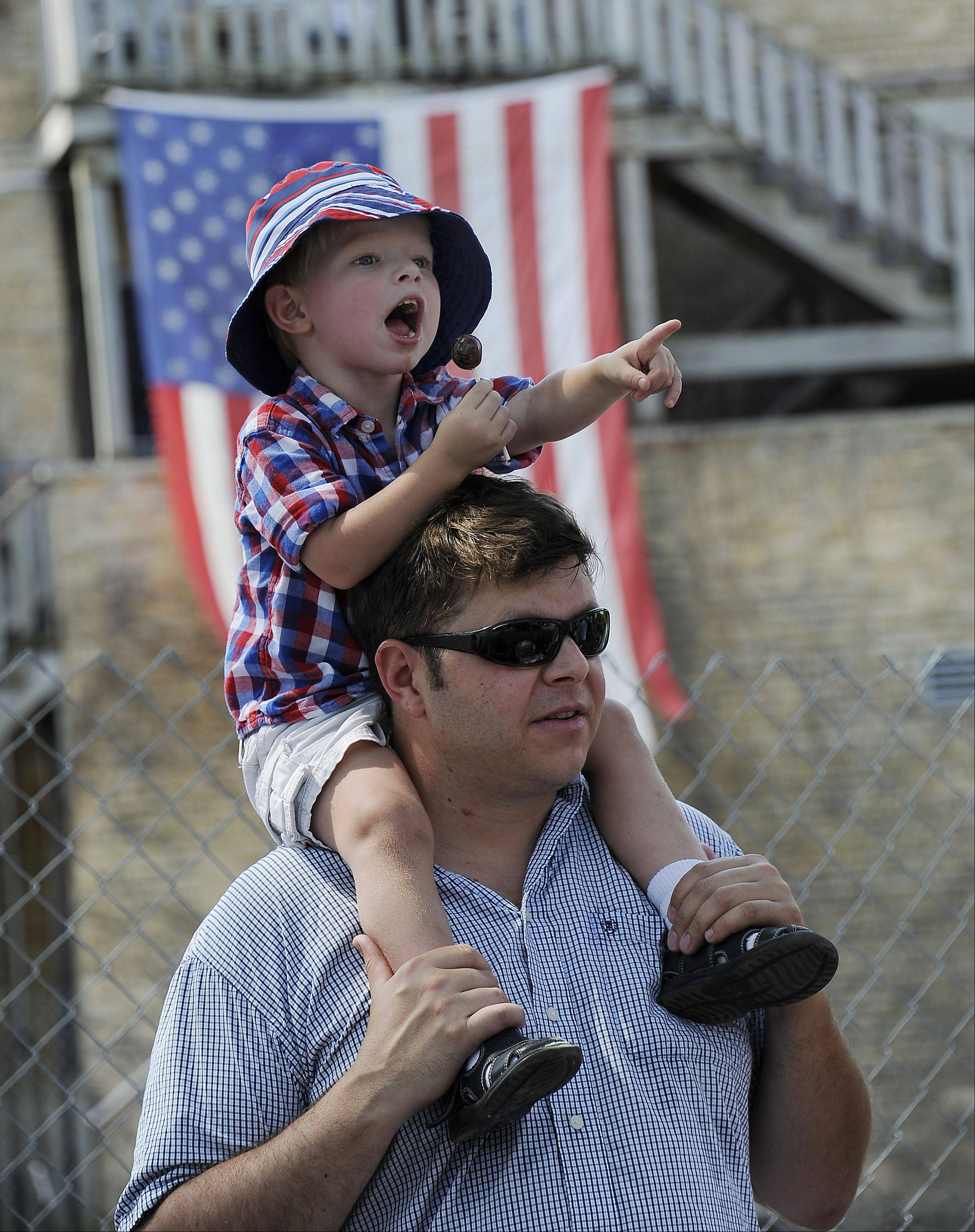 Aidan Nagy, 2, of Arlington Heights points out what he likes in the Fourth of July parade while dad, Steve provides a higher vantage point during the parade on Wednesday in Arlington Heights.
