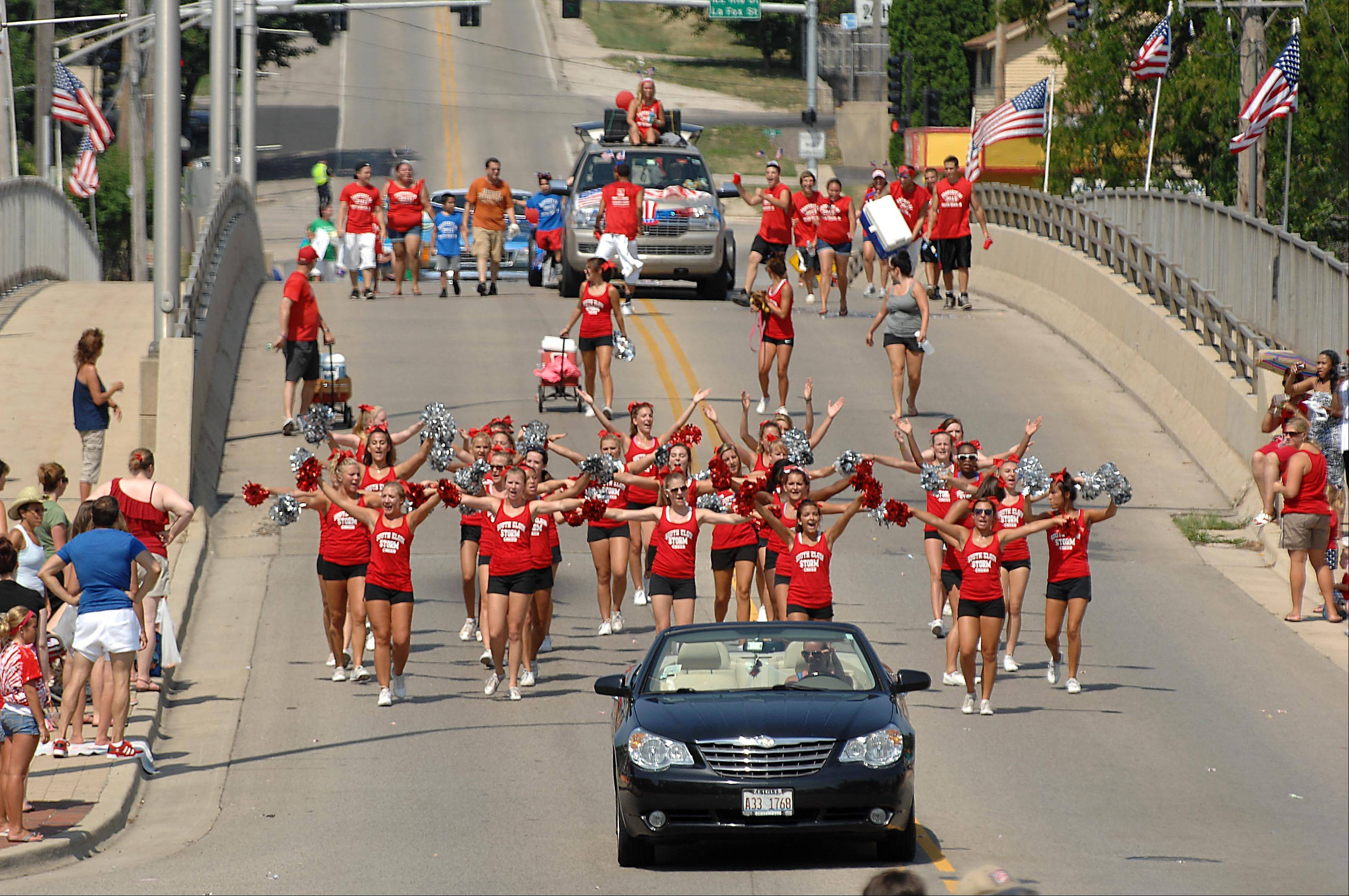 The South Elgin High School cheerleaders march over the Fox River bridge Wednesday at the South Elgin Fourth of July parade.