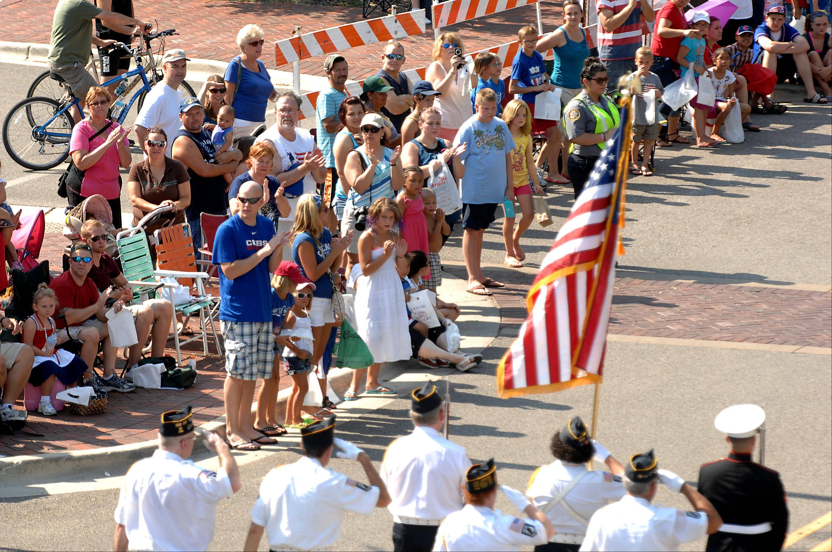 The crowd stands and applauds as the American Flag passes Wednesday at Elgin Fourth of July parade.