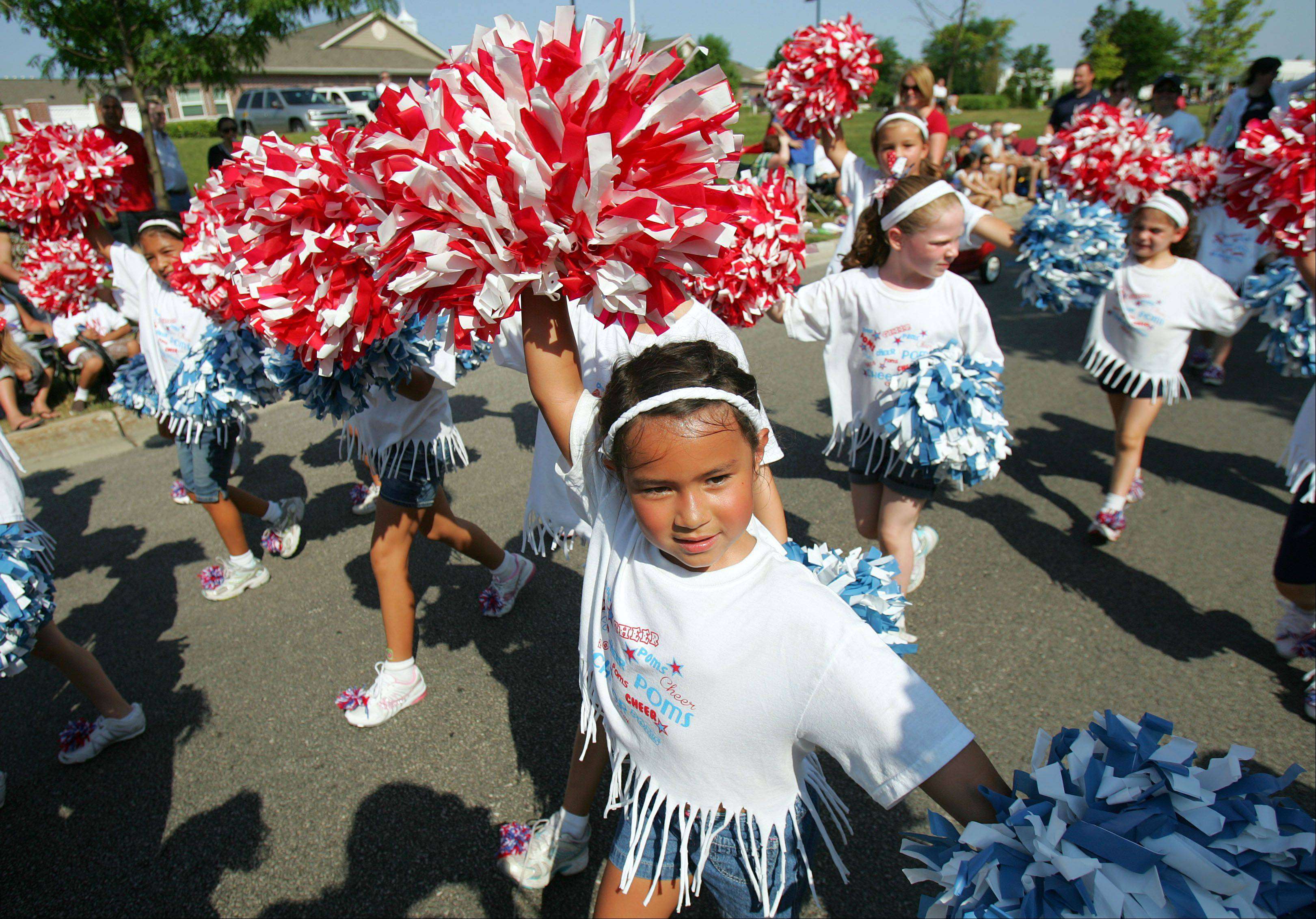 The Vernon Hills Park District poms and cheer perform for the crowd during the Vernon Hills Fourth of July Parade Wednesday morning on Deerpath Drive.