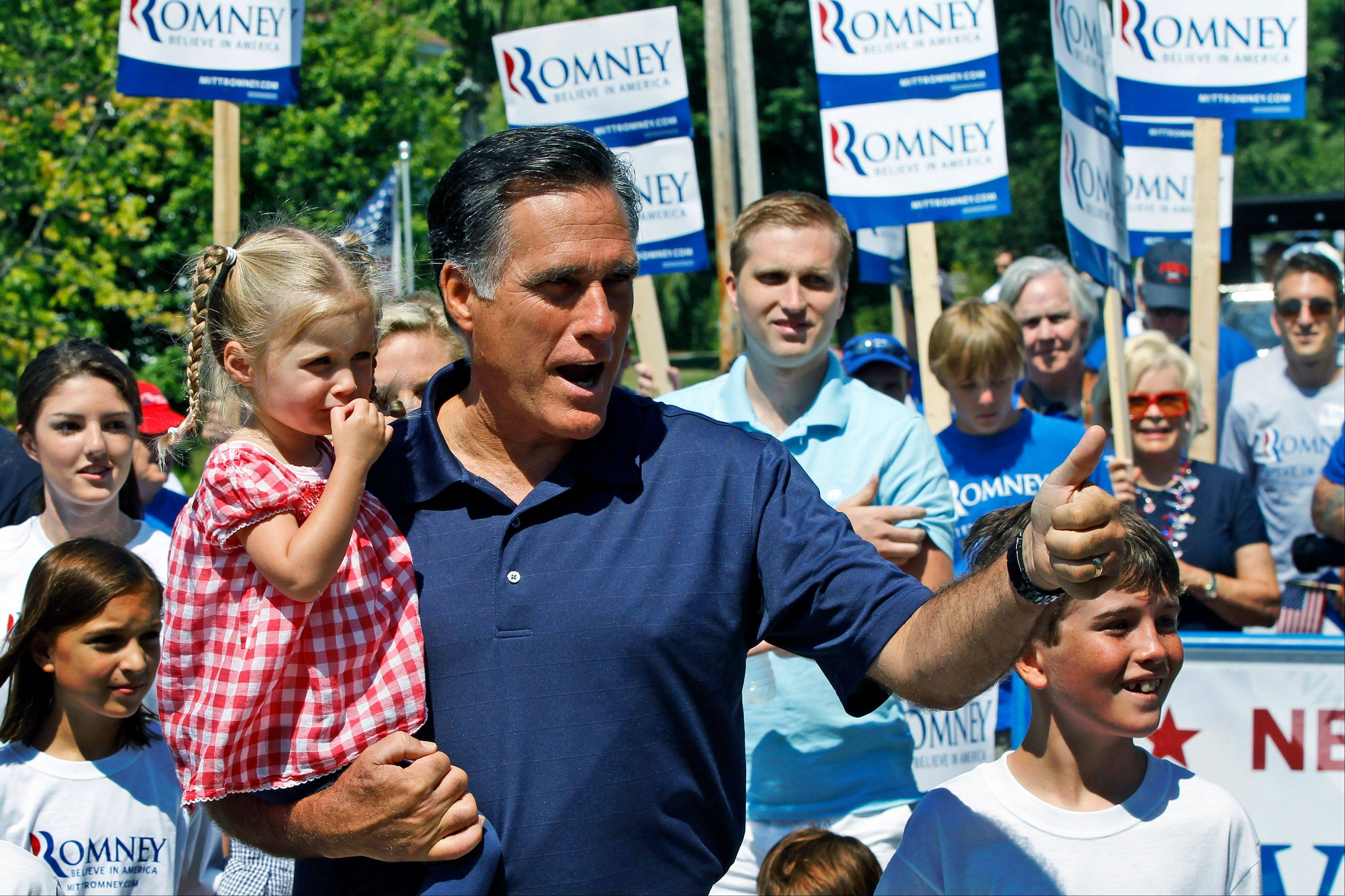 Republican presidential candidate, former Massachusetts Gov. Mitt Romney gives a thumbs up as he carries his granddaughter, Soleil, while walking in the Fourth of July Parade in Wolfeboro, N.H., Wednesday.