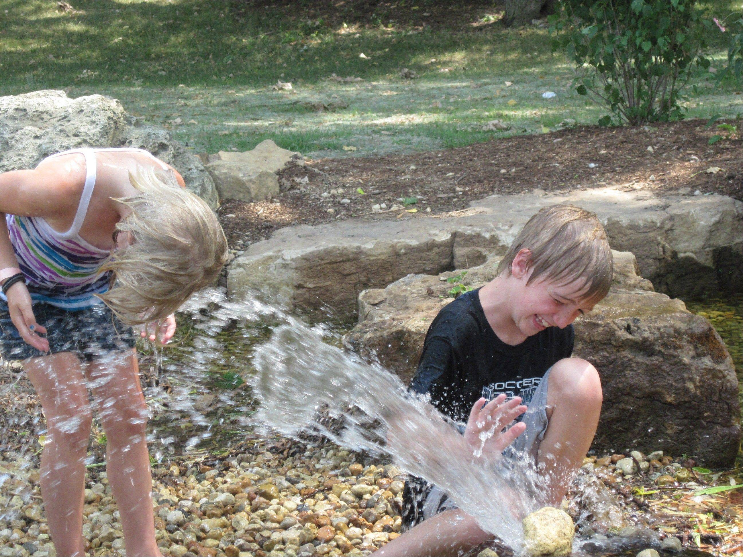 "Siblings Emerson, left, and Kaiden Massie of Aurora enjoy the new ""Water Wonders"" stream Tuesday at Island Park in North Aurora."