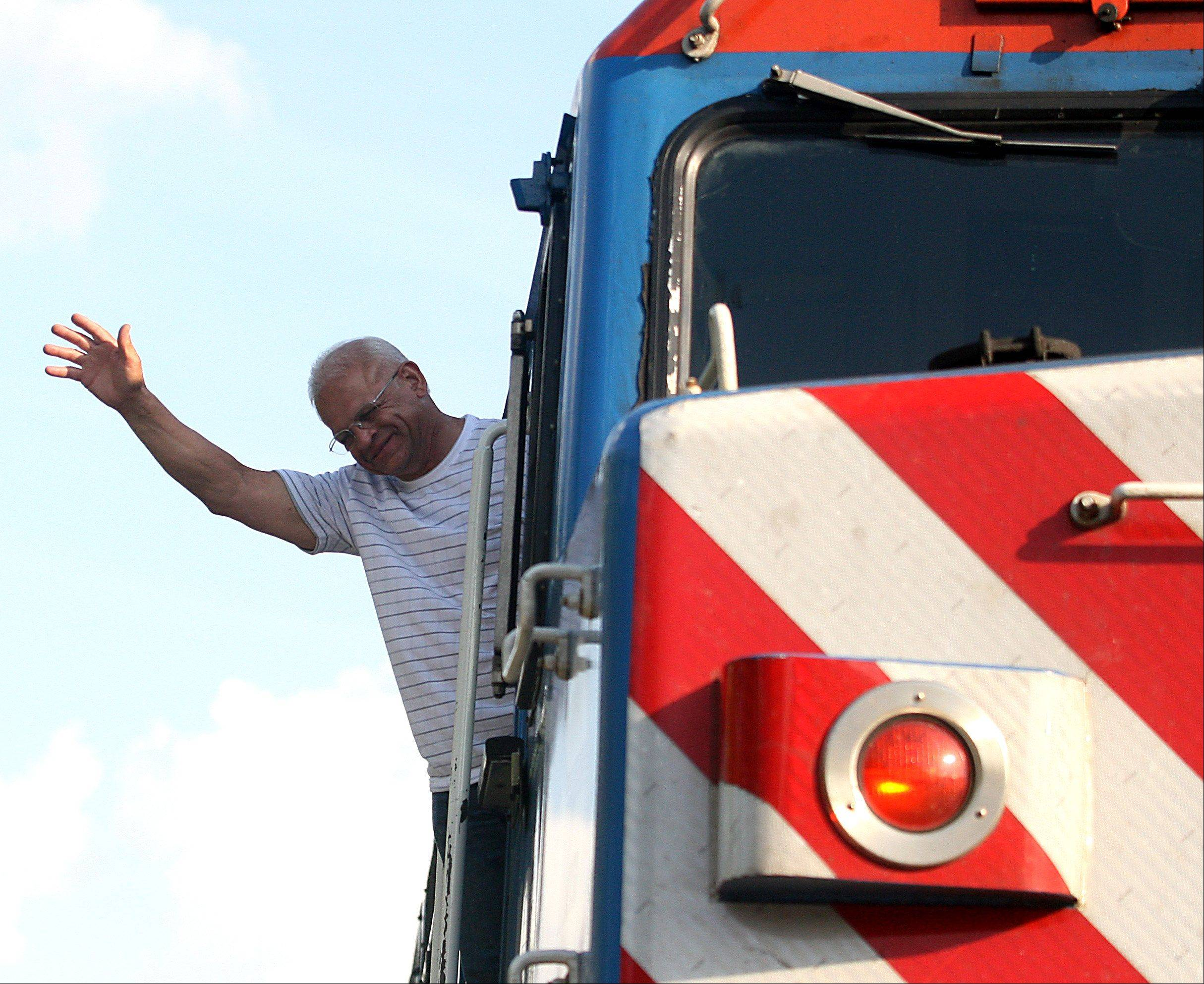 Metra engineer Hector Feliciano waves from his perch atop an engine after piloting a train for the final time upon arrival at the Chicago Street Station in Elgin on Tuesday evening.