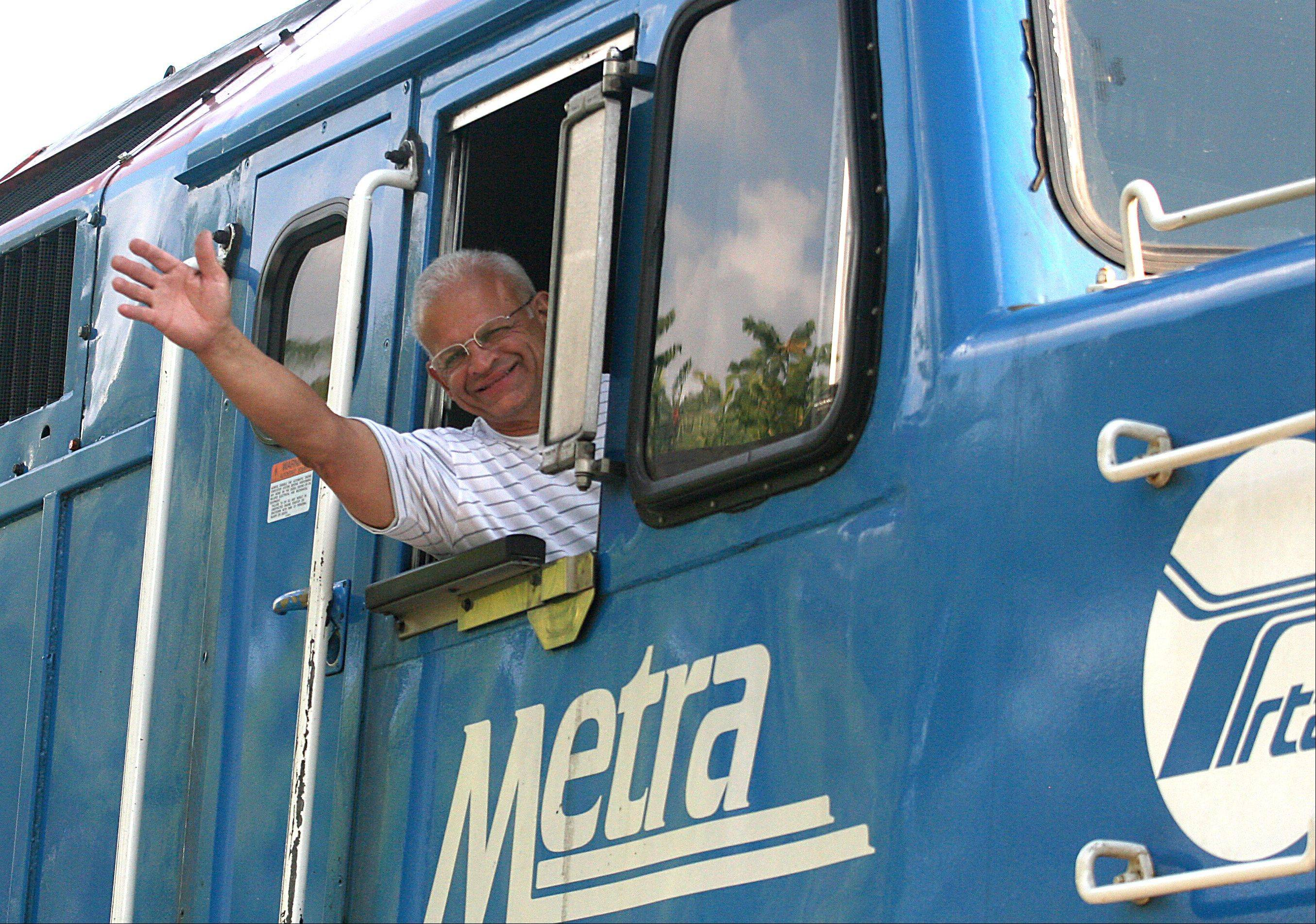 Metra engineer Hector Feliciano smiles after piloting a train for the final time upon arrival at the Chicago Street Station in Elgin on Tuesday. Feliciano retired after 42 years of service.