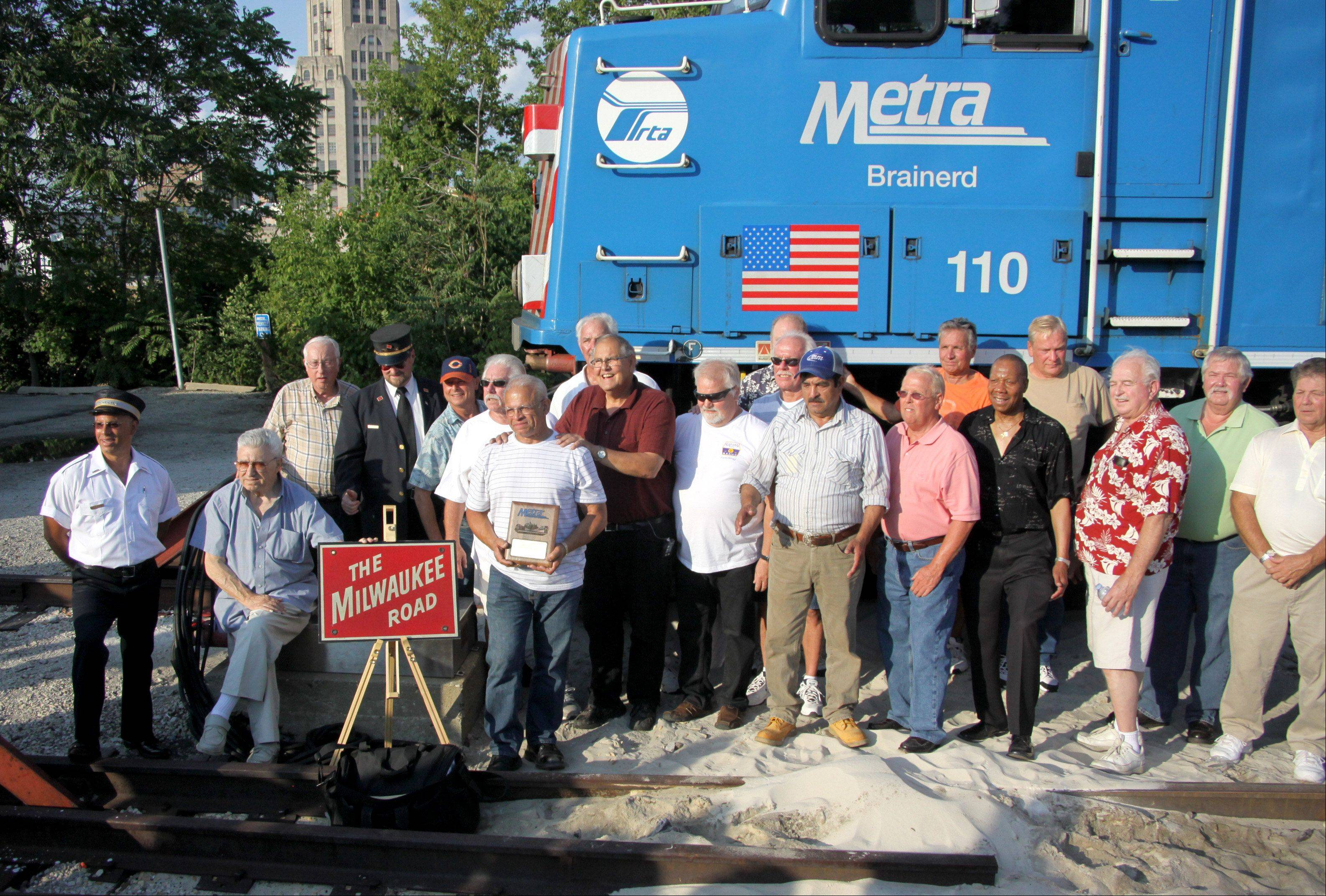 Metra engineer Hector Feliciano poses with several retired and current Metra personnel after Feliciano piloted a train for the final time upon arrival at the Chicago Street Station in Elgin on Tuesday evening. Feliciano retired after 42 years of service.