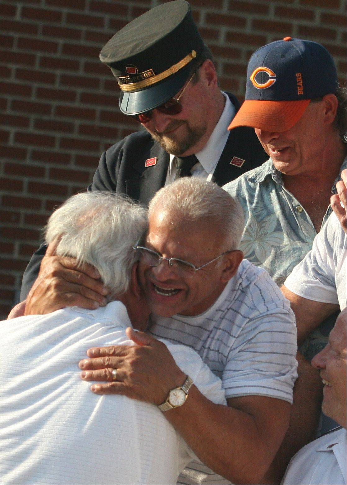 Metra engineer Hector Feliciano retired after piloting a train for the final time upon arrival at the Chicago Street Station in Elgin on Tuesday evening. Here, Feliciano greets friends gathered to wish him well.