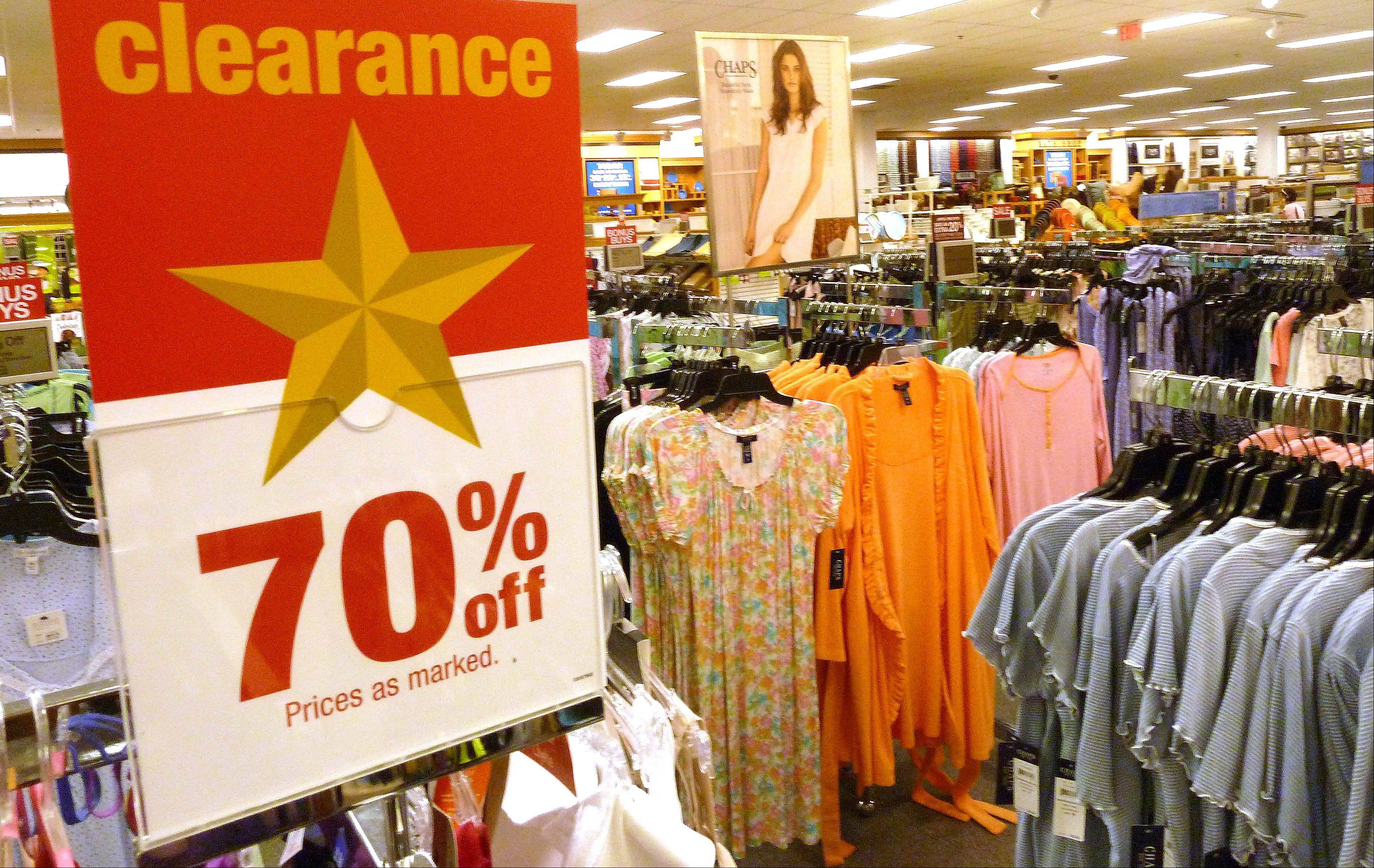 Shirts and blouse hang on racks at a clothing store in North Andover, Mass. American shoppers, worried about jobs and the overall economy, pulled back on spending in June, resulting in tepid sales for many retailers.